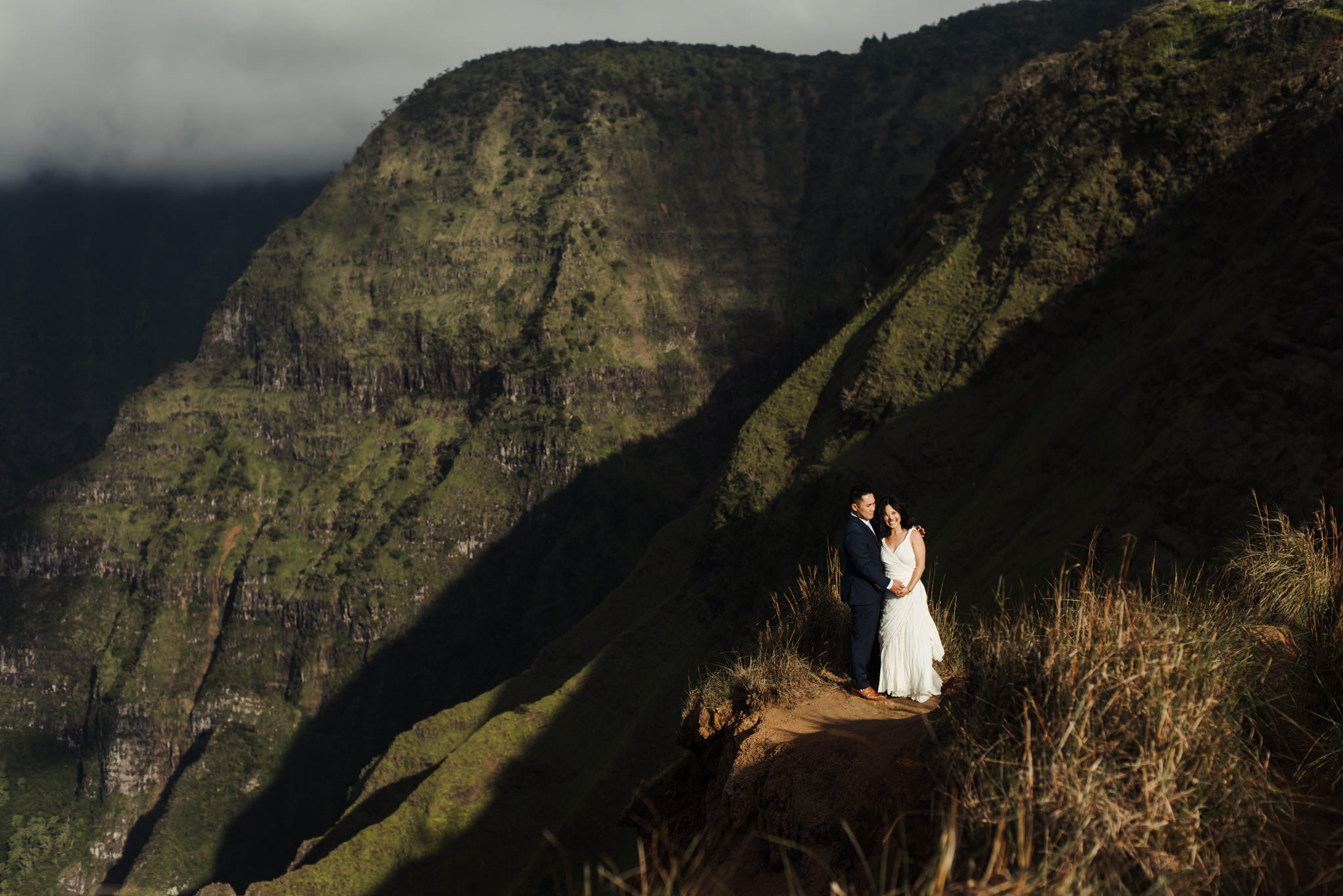 Bride and groom standing in front of cliffs in Kauai elopement