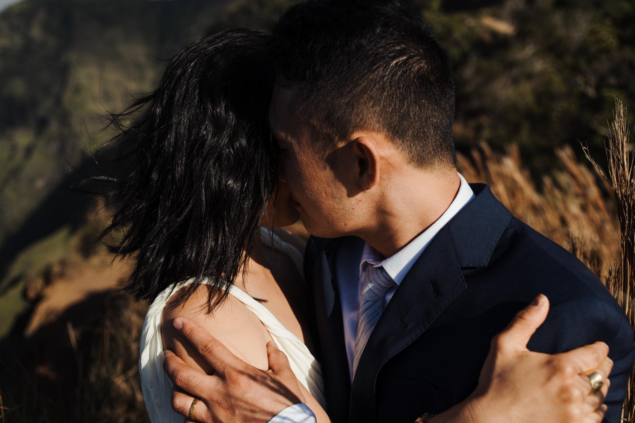 bride and groom kissing in sunlight in Kauai