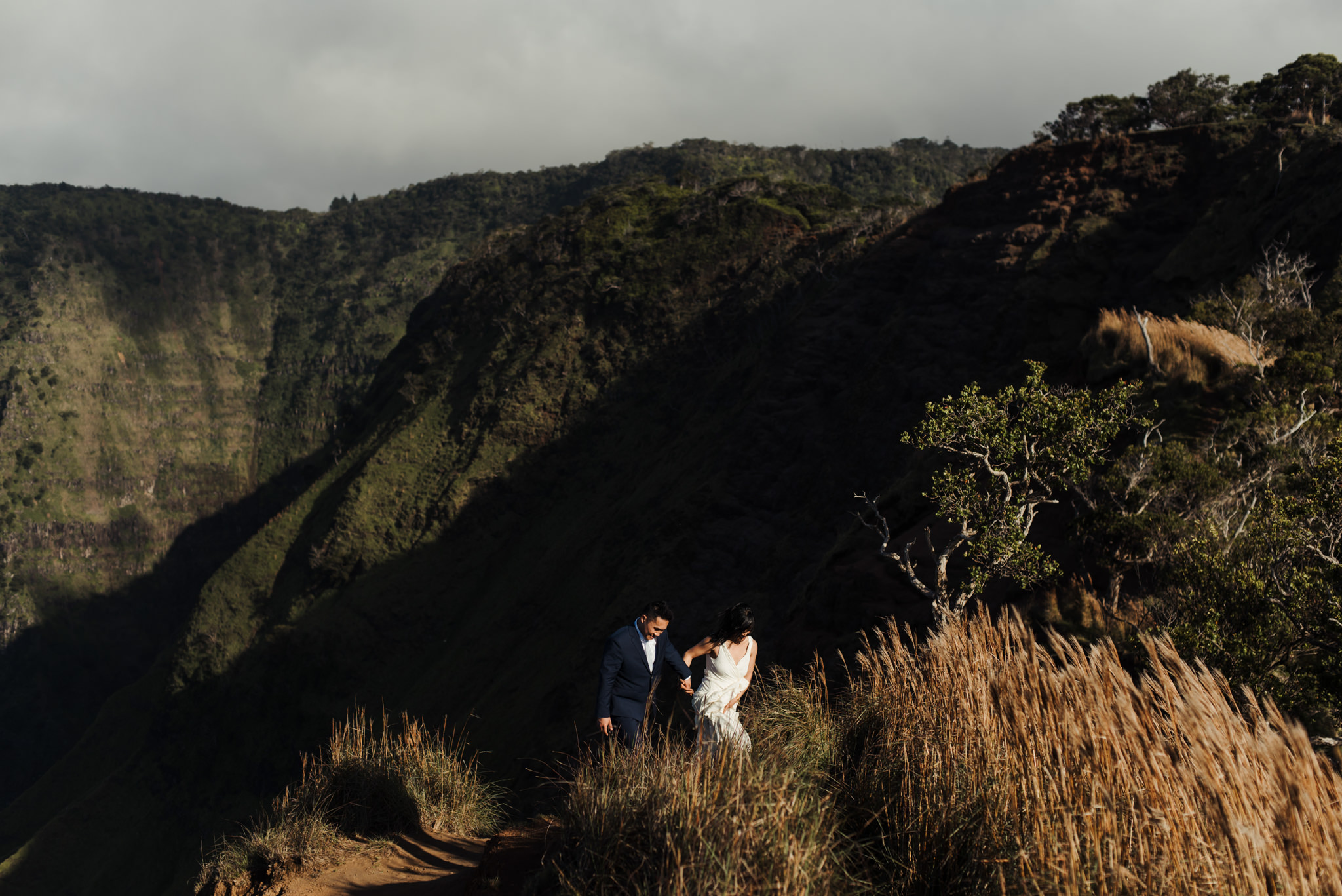 Bride and groom hiking up cliff side in Kokee State Park in Kauai