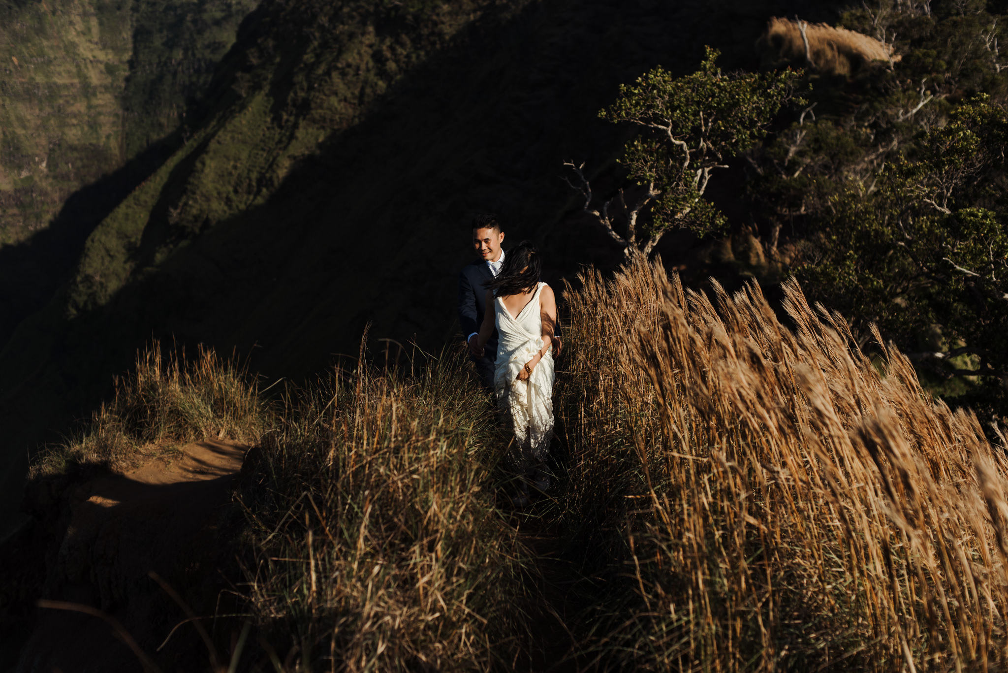 Bride and groom walking on hiking trail in Kokee State Park