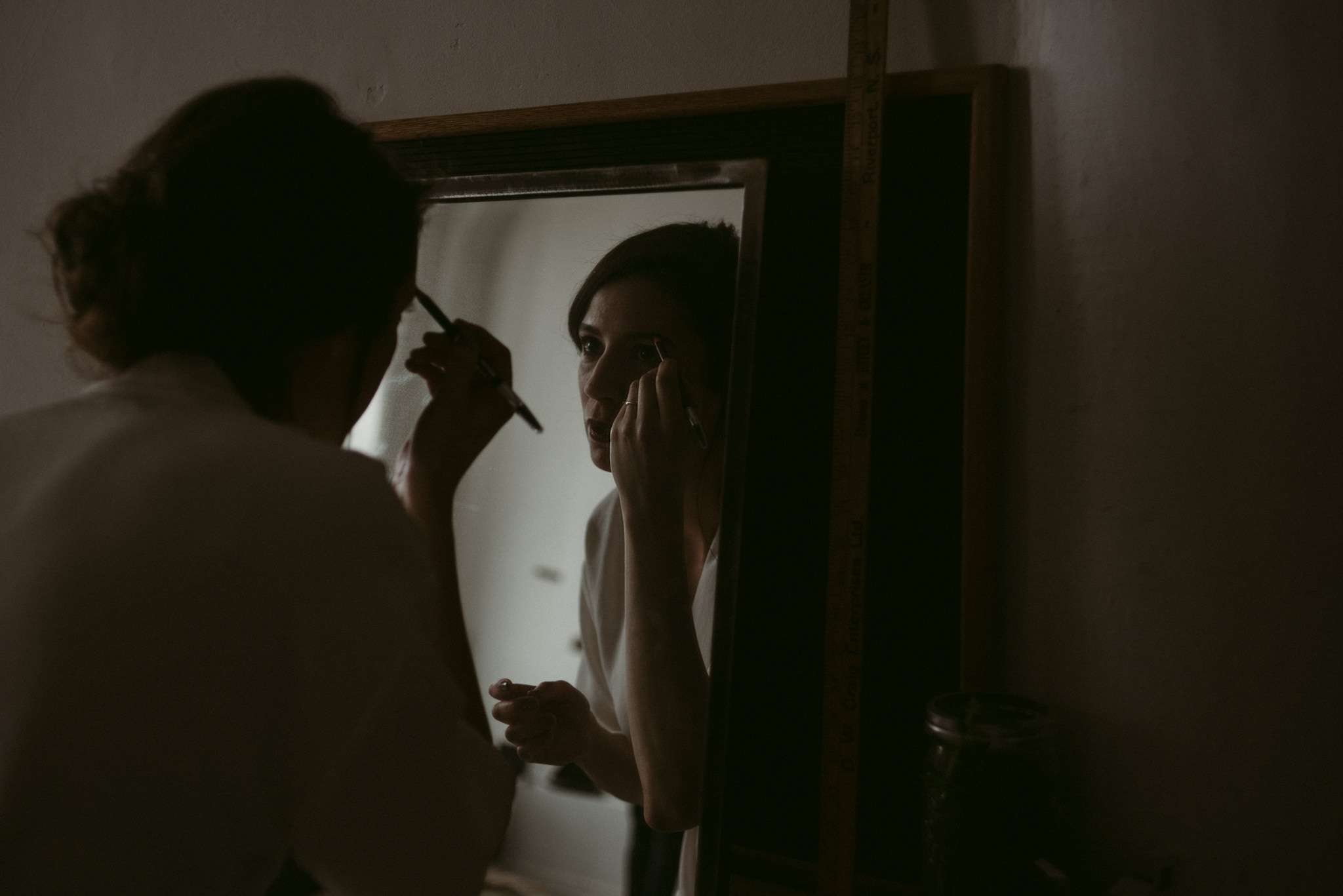 Bride looking in mirror doing makeup