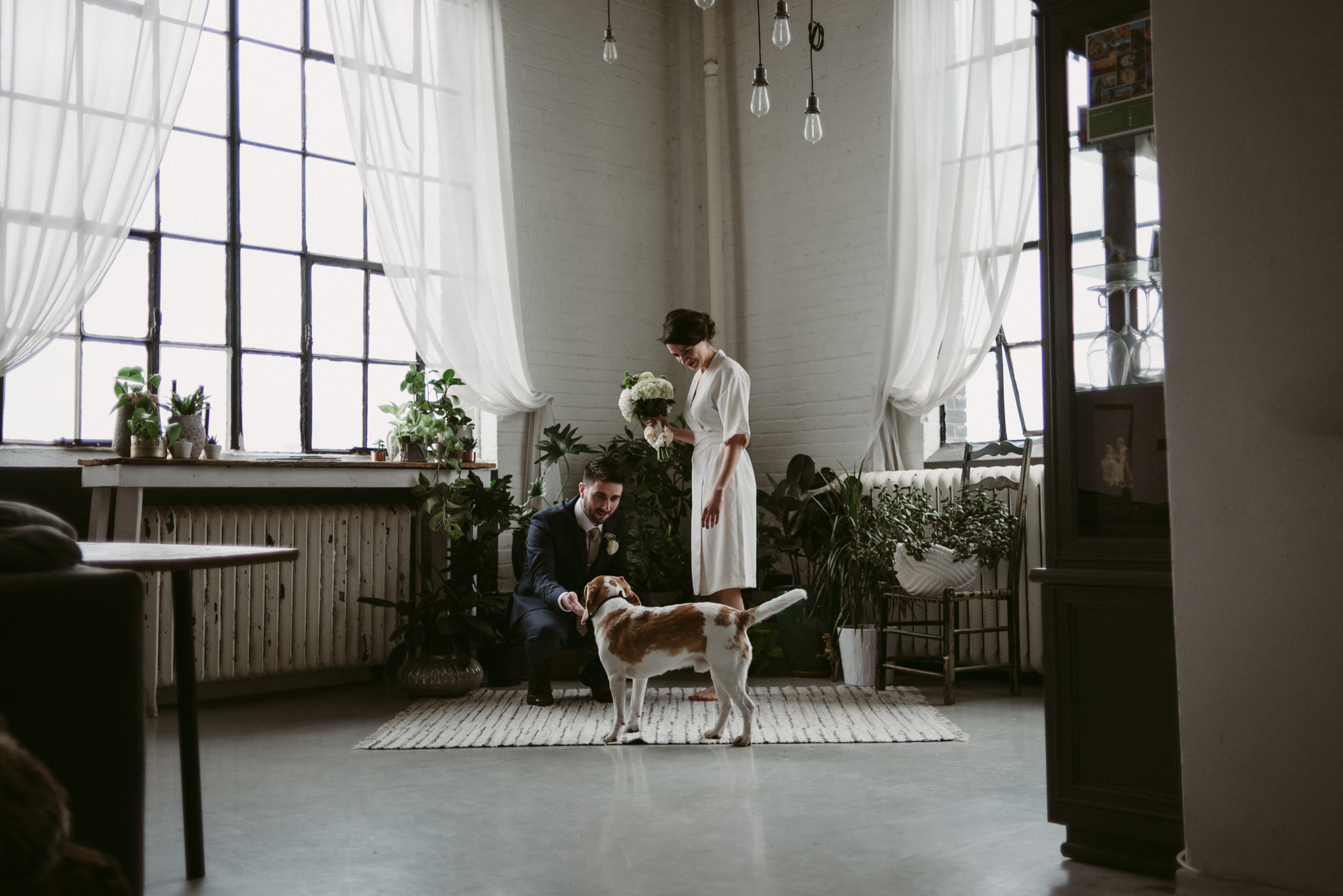 Bride and groom with dog in loft