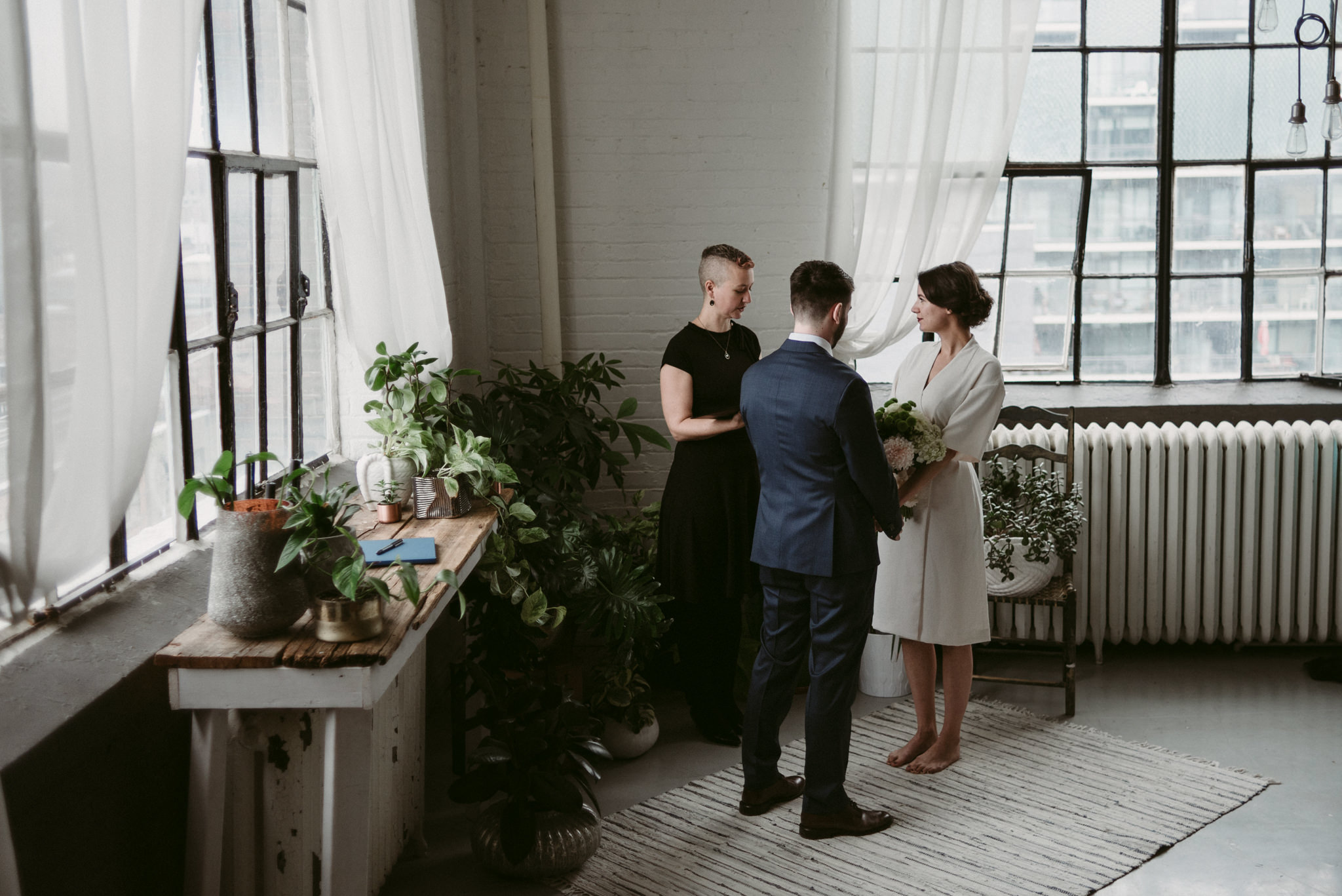 Bride and groom during elopement ceremony in trendy loft