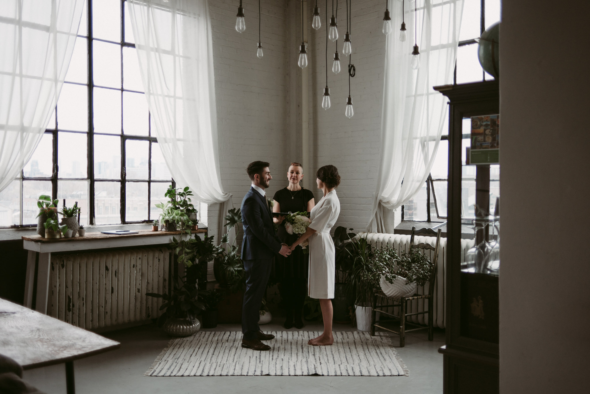 Bride and groom holding hands during ceremony in trendy Toronto loft