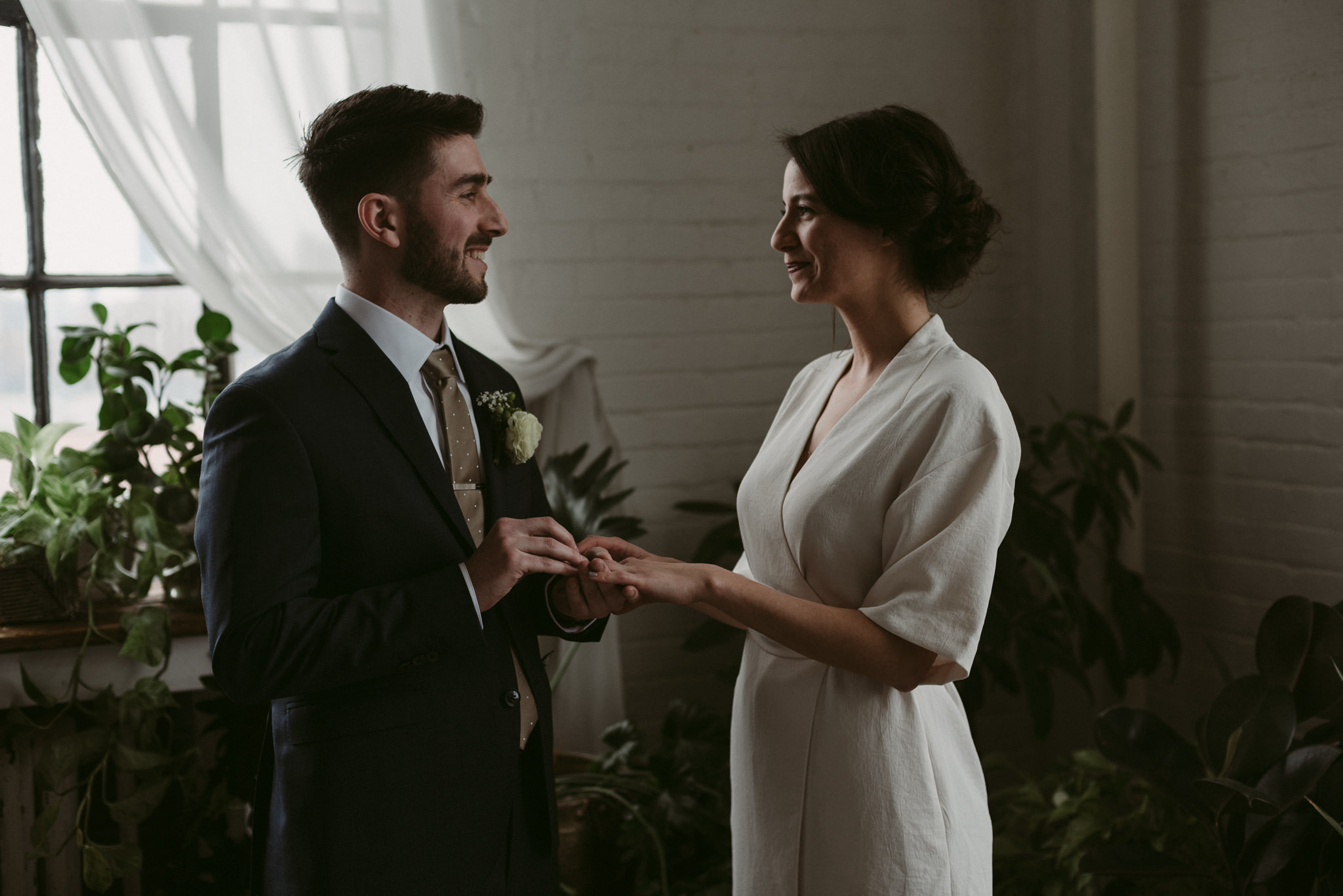 Bride and groom exchanging rings, Toronto loft elopement