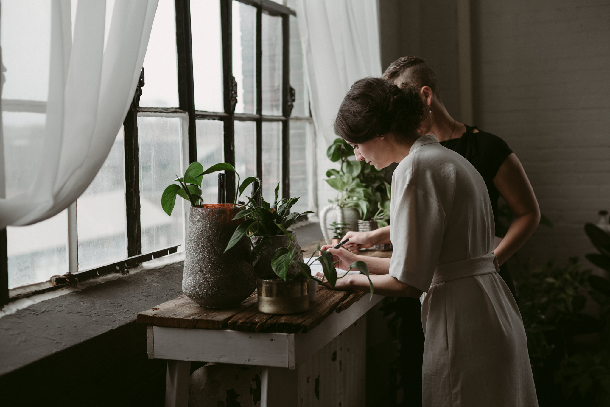 Bride signing marriage license in cool Toronto loft with large windows