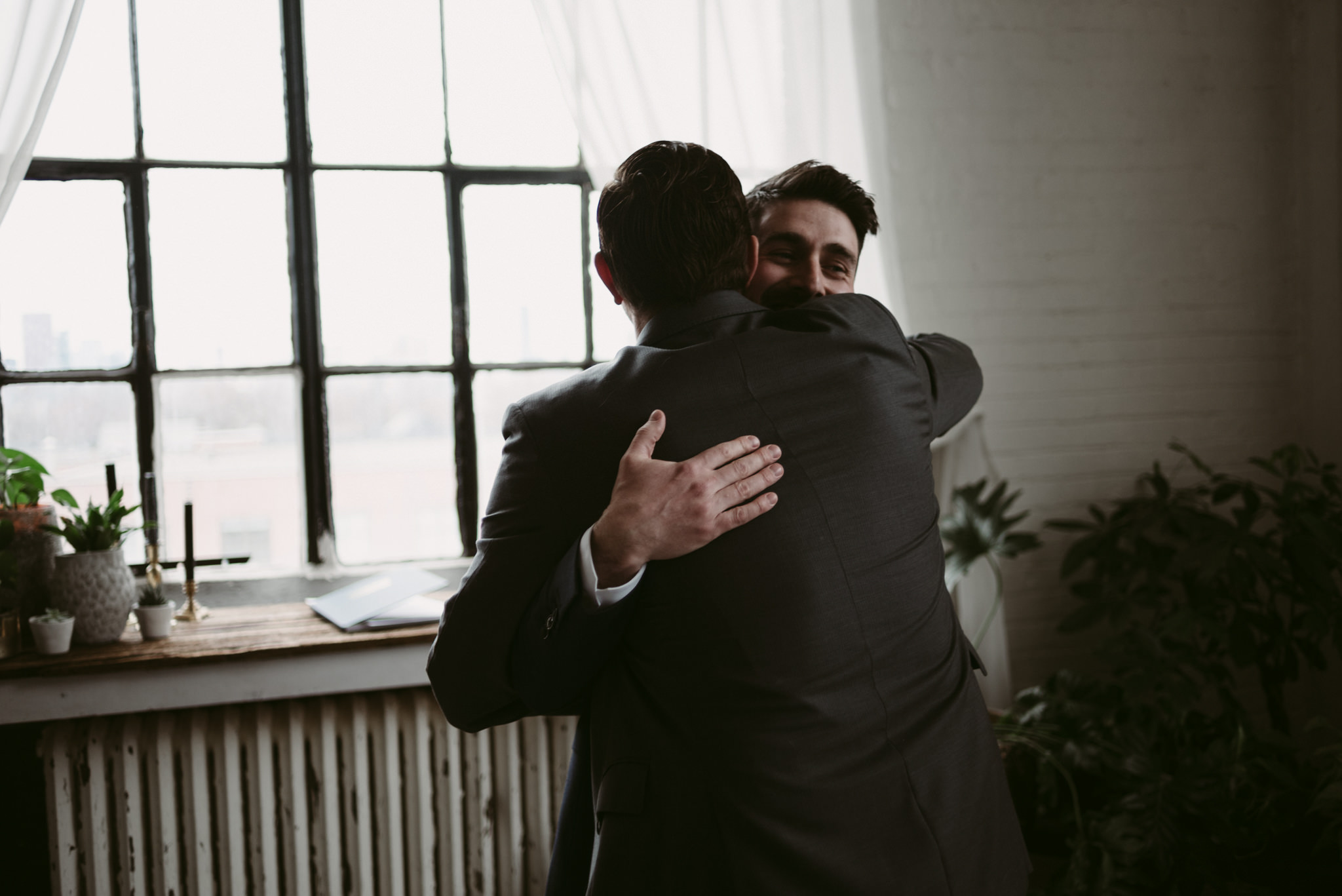 groom hugging friend after the ceremony in loft