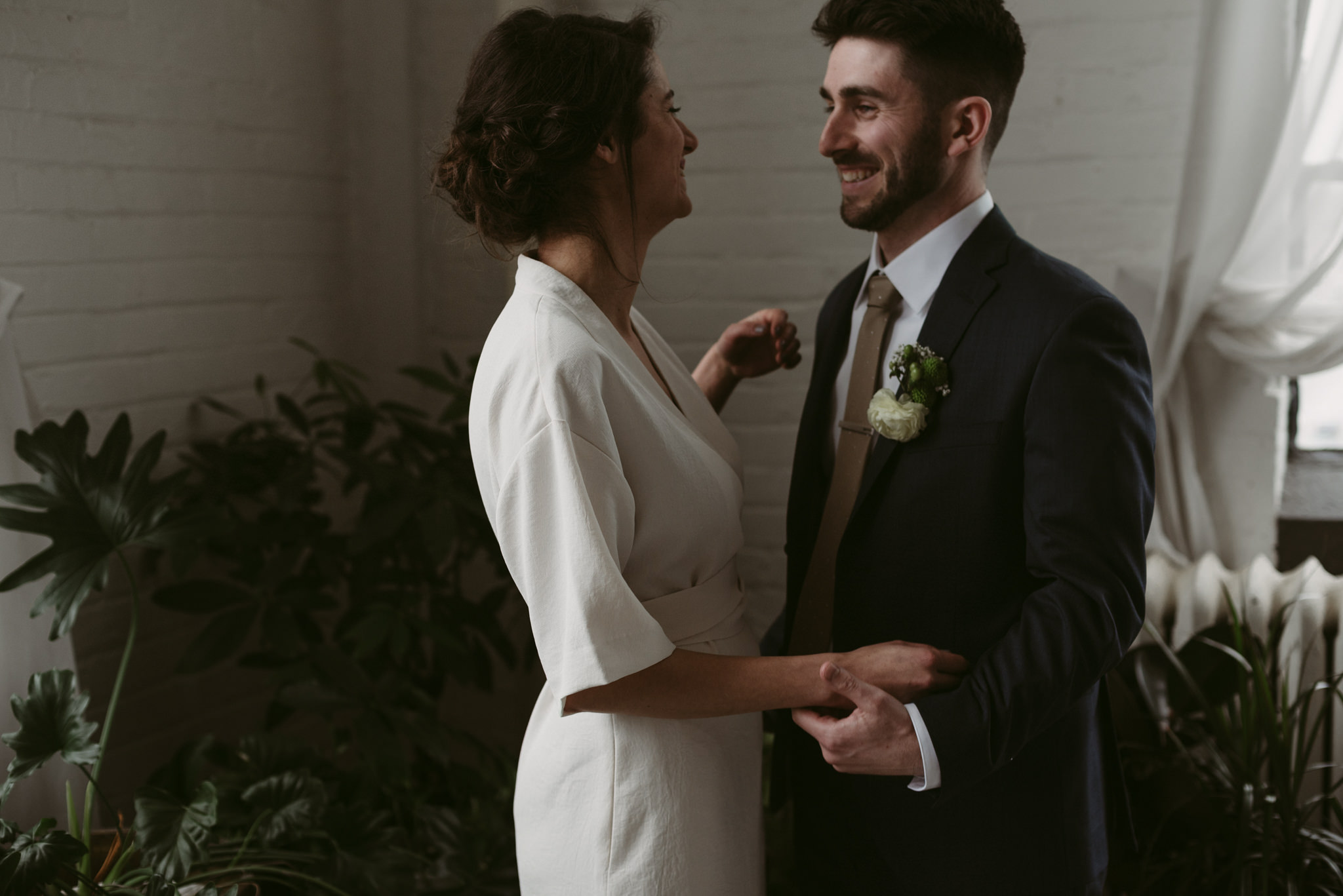 Bride and groom laughing in loft with plants