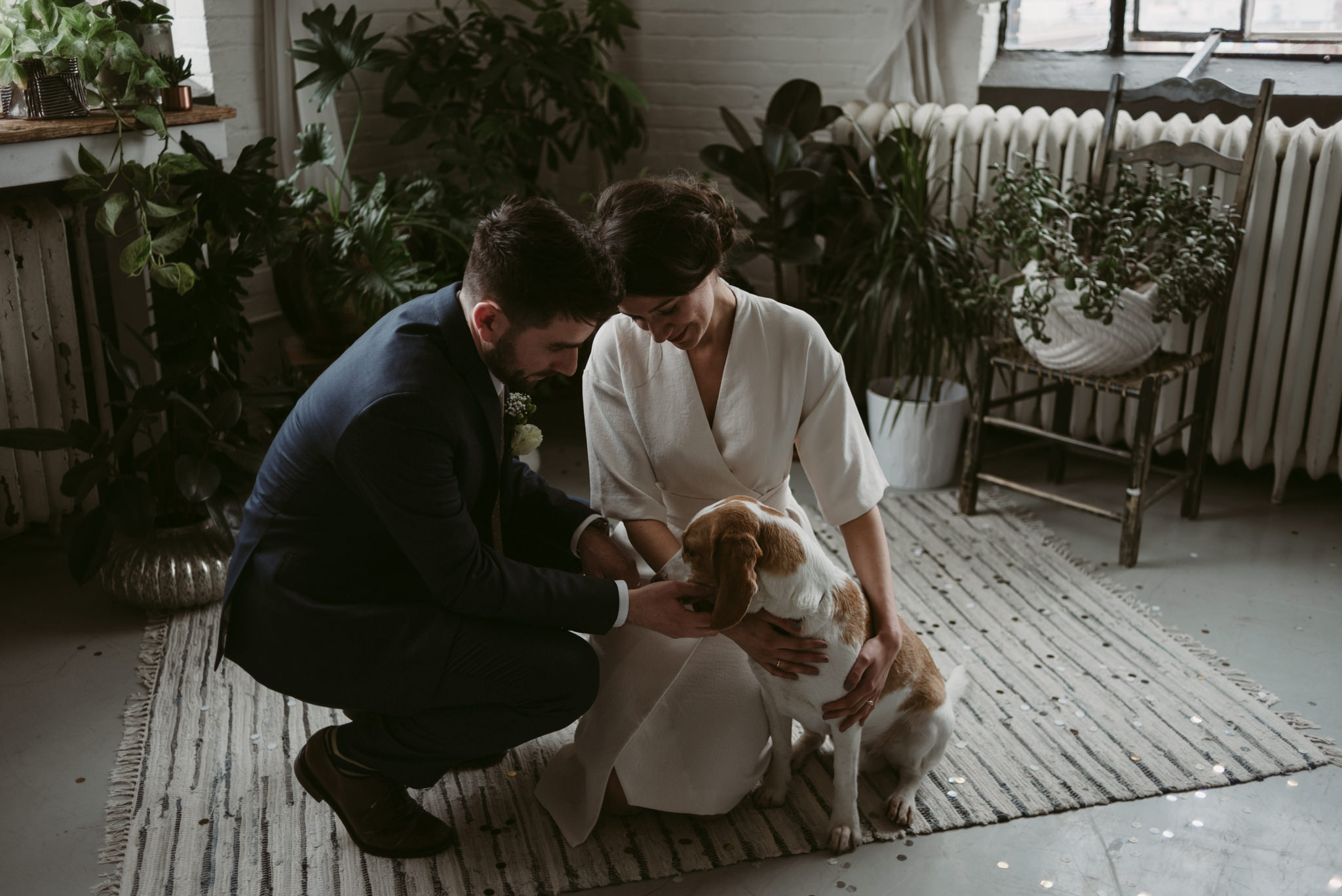 Bride and groom petting dog in loft