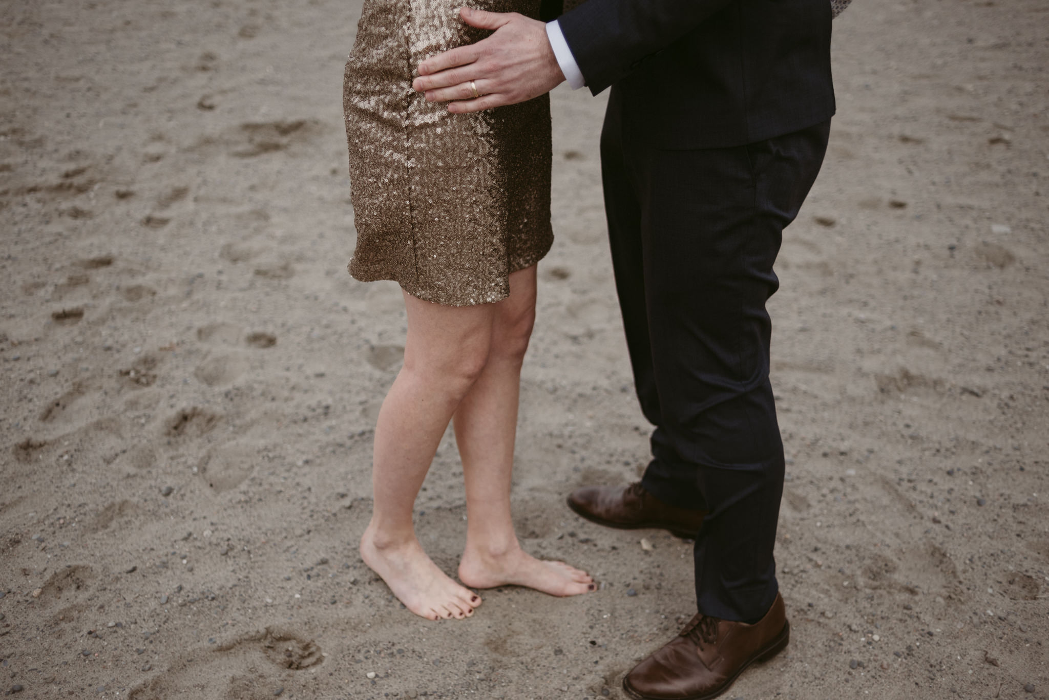 Couple hugging, woman barefoot in sand