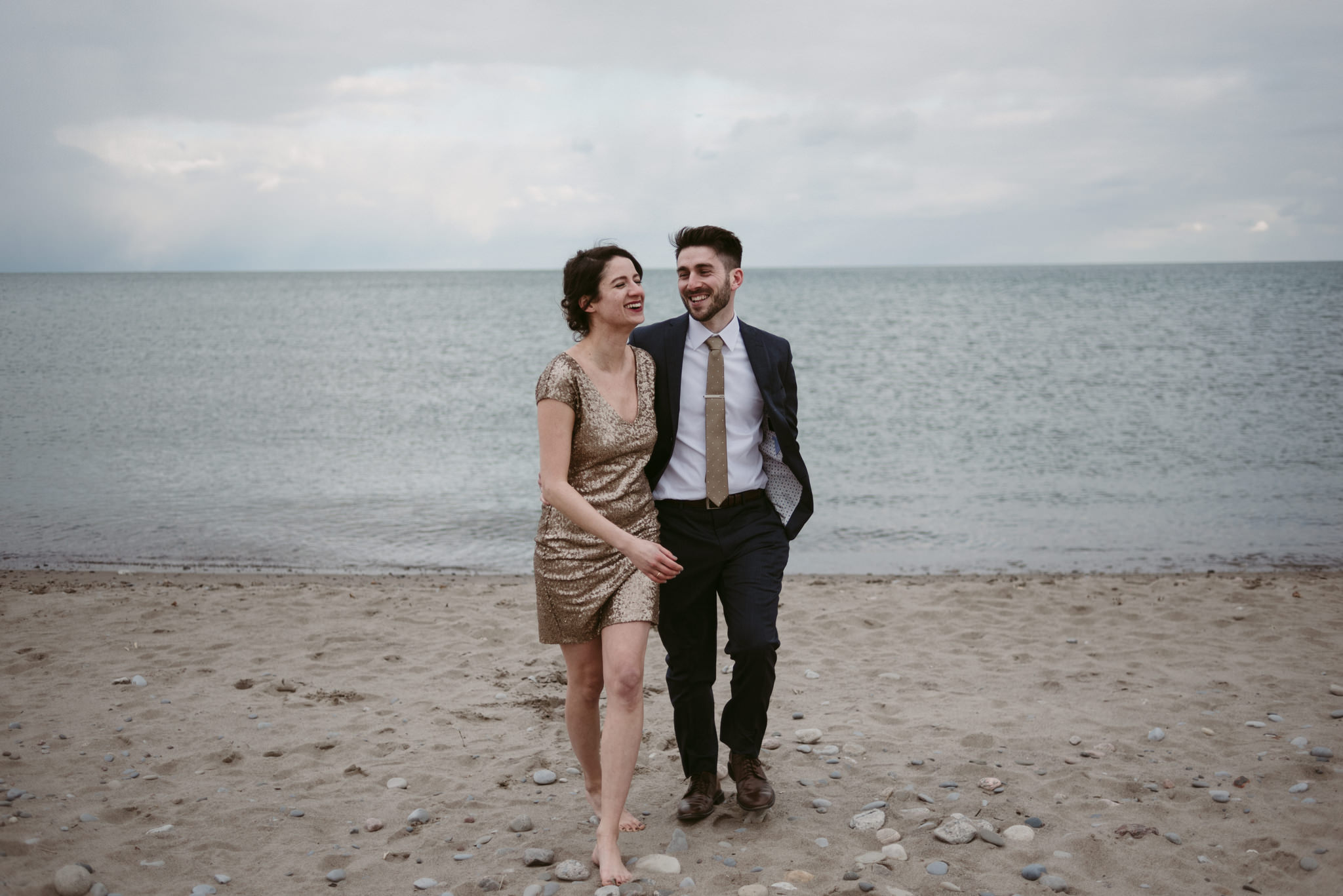 Couple walking and laughing on the beach