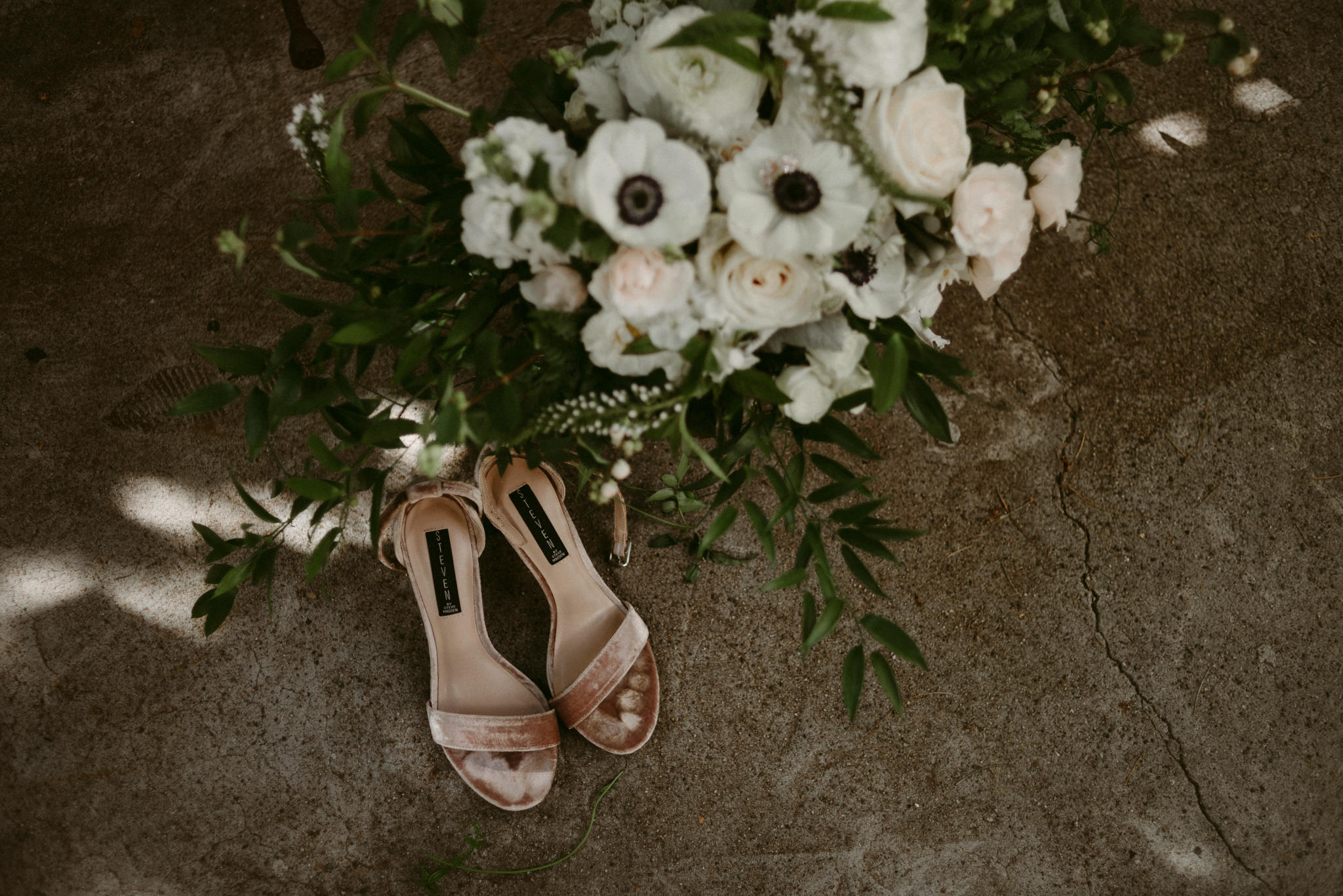 velvet shoes and wedding bouquet on concrete floor