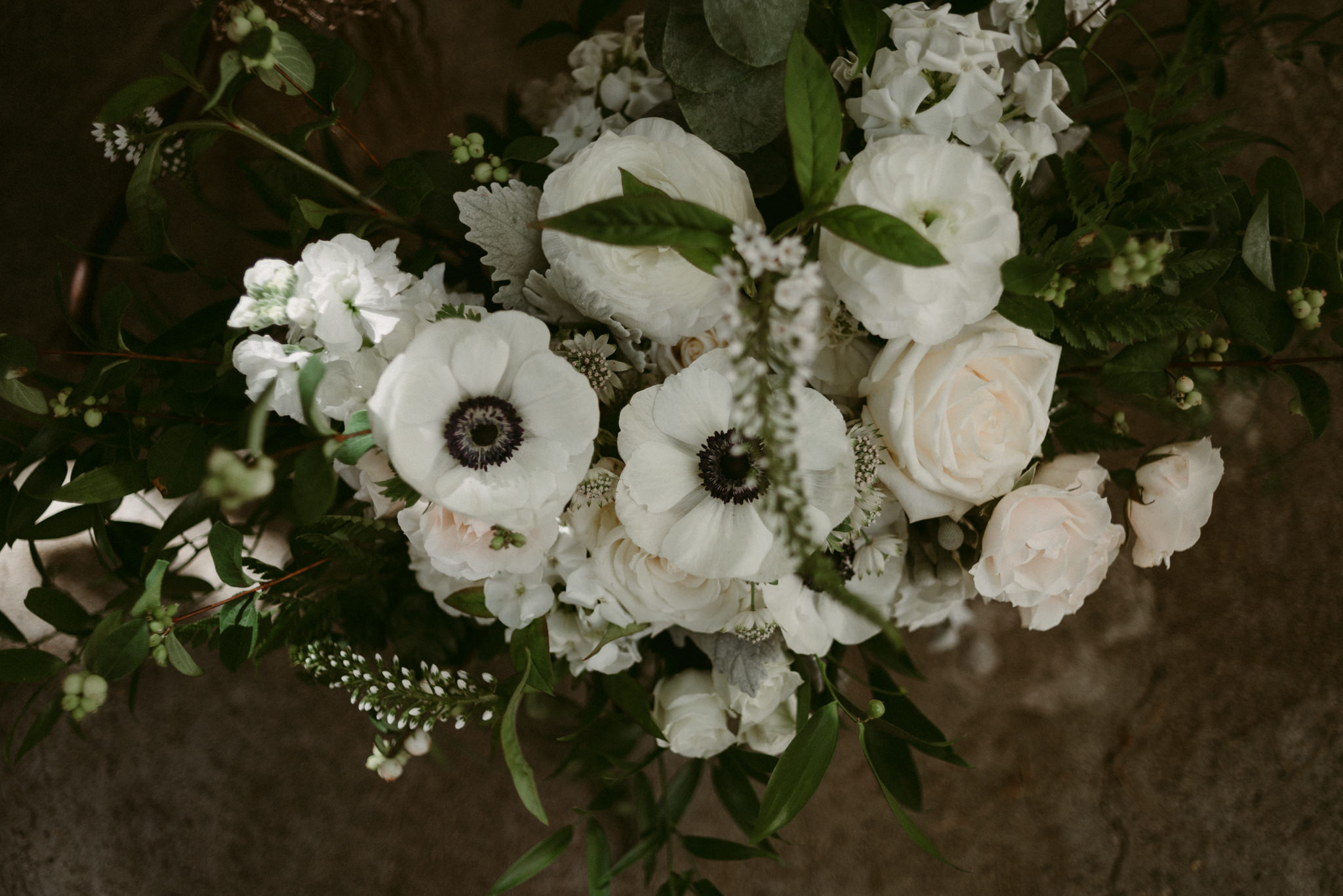 close up of white roses and poppies in wedding bouquet