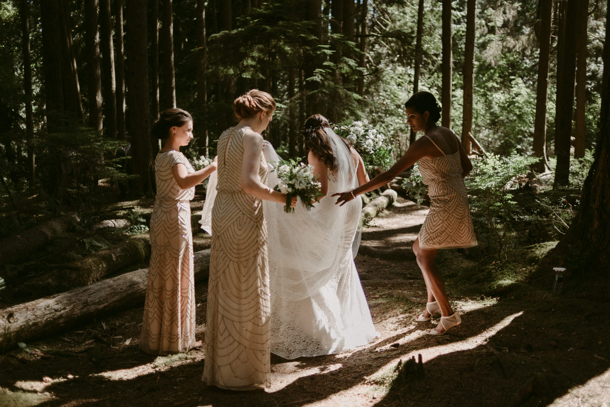 bridesmaids helping bride with dress in forest