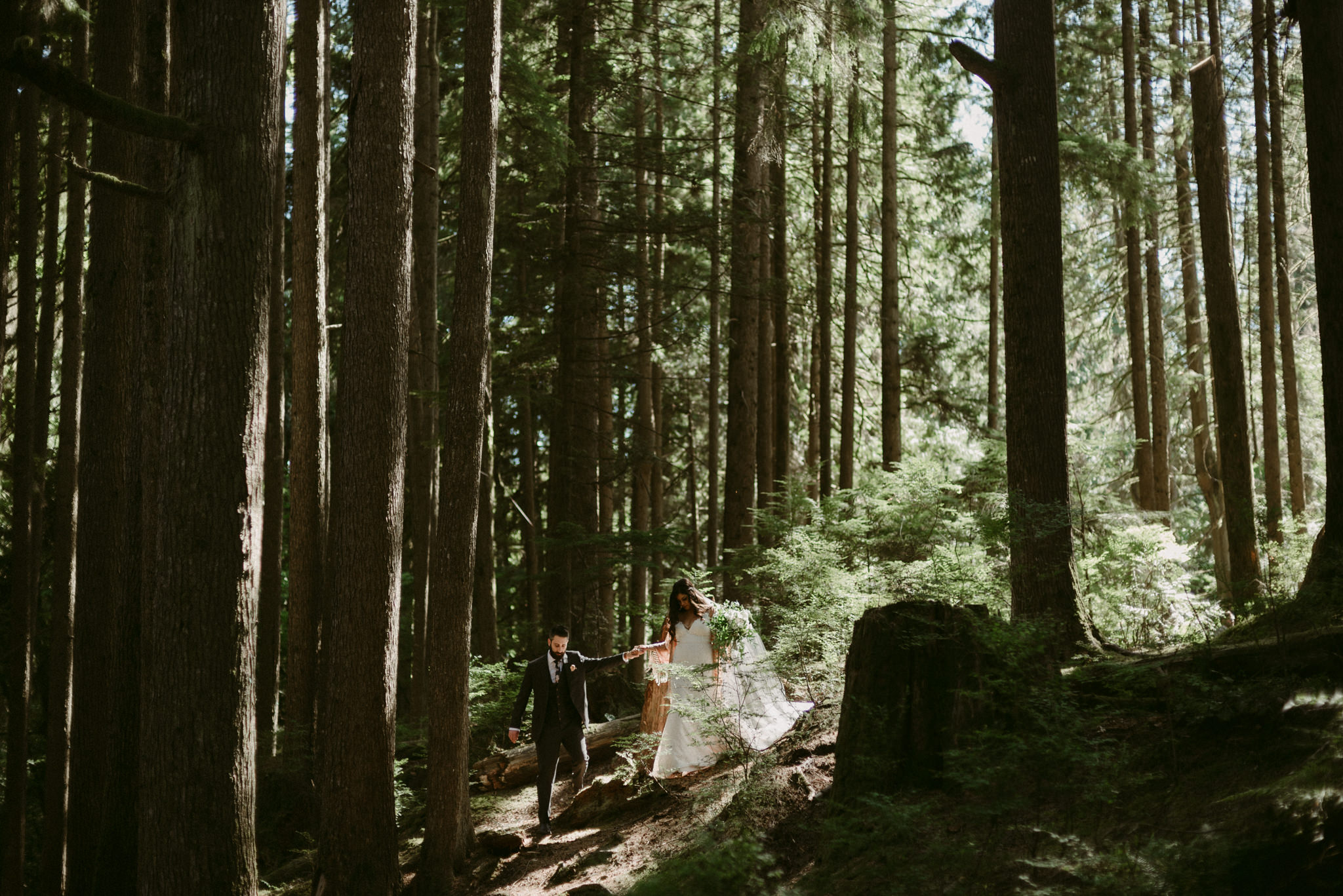 Bride and groom walking in light filled forest
