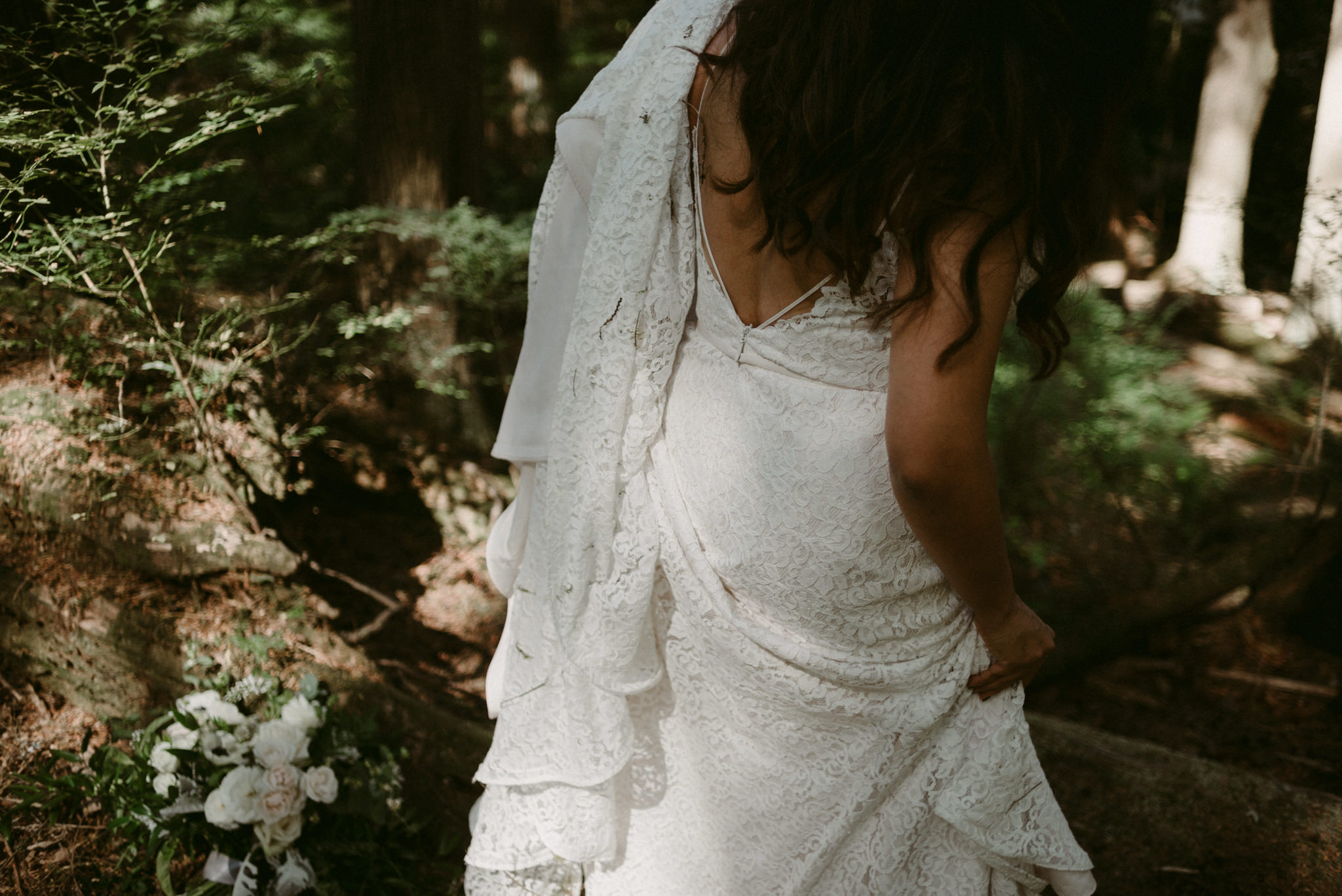 bride walking while holding dress in forest