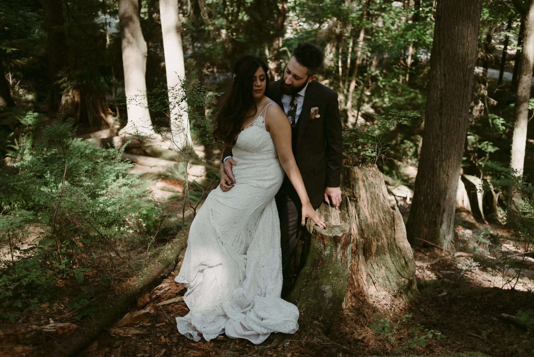 bride and groom sitting on tree stump on forest