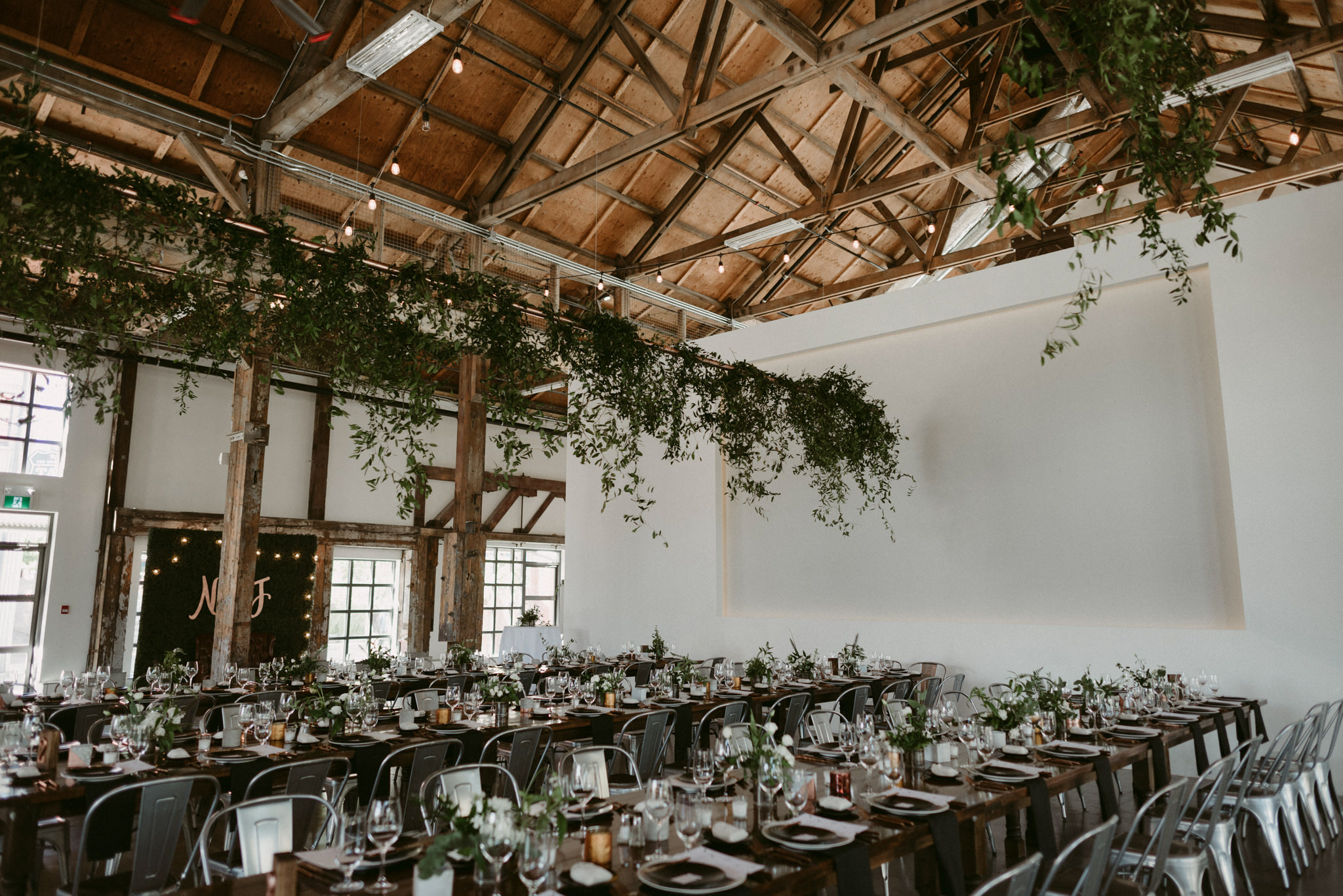 hanging vines and table seting in industrial wedding venue