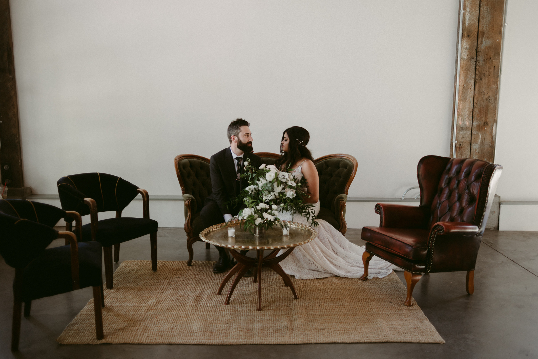 couple sitting on couch on wedding day