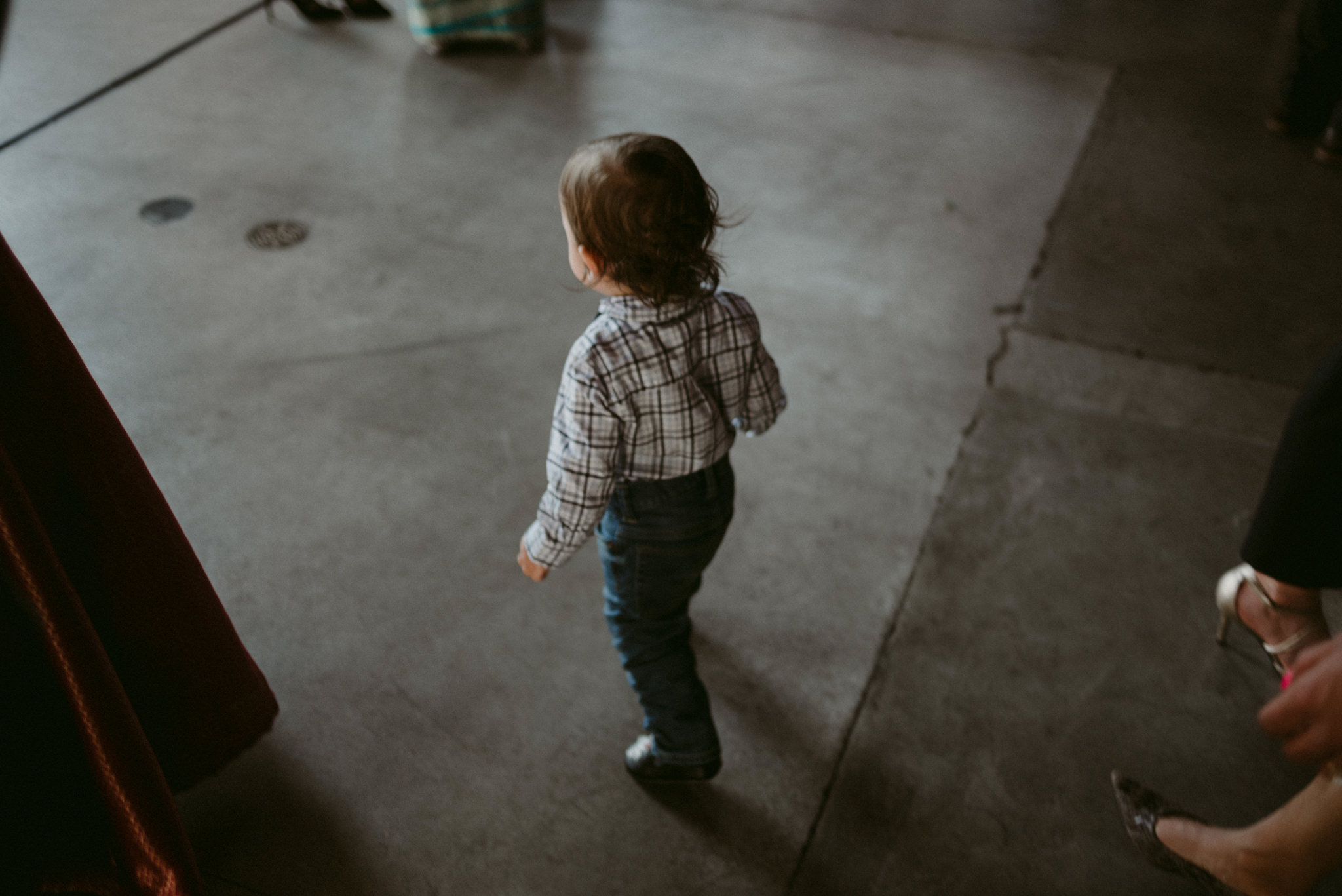 little boy walking on concrete floor at wedding