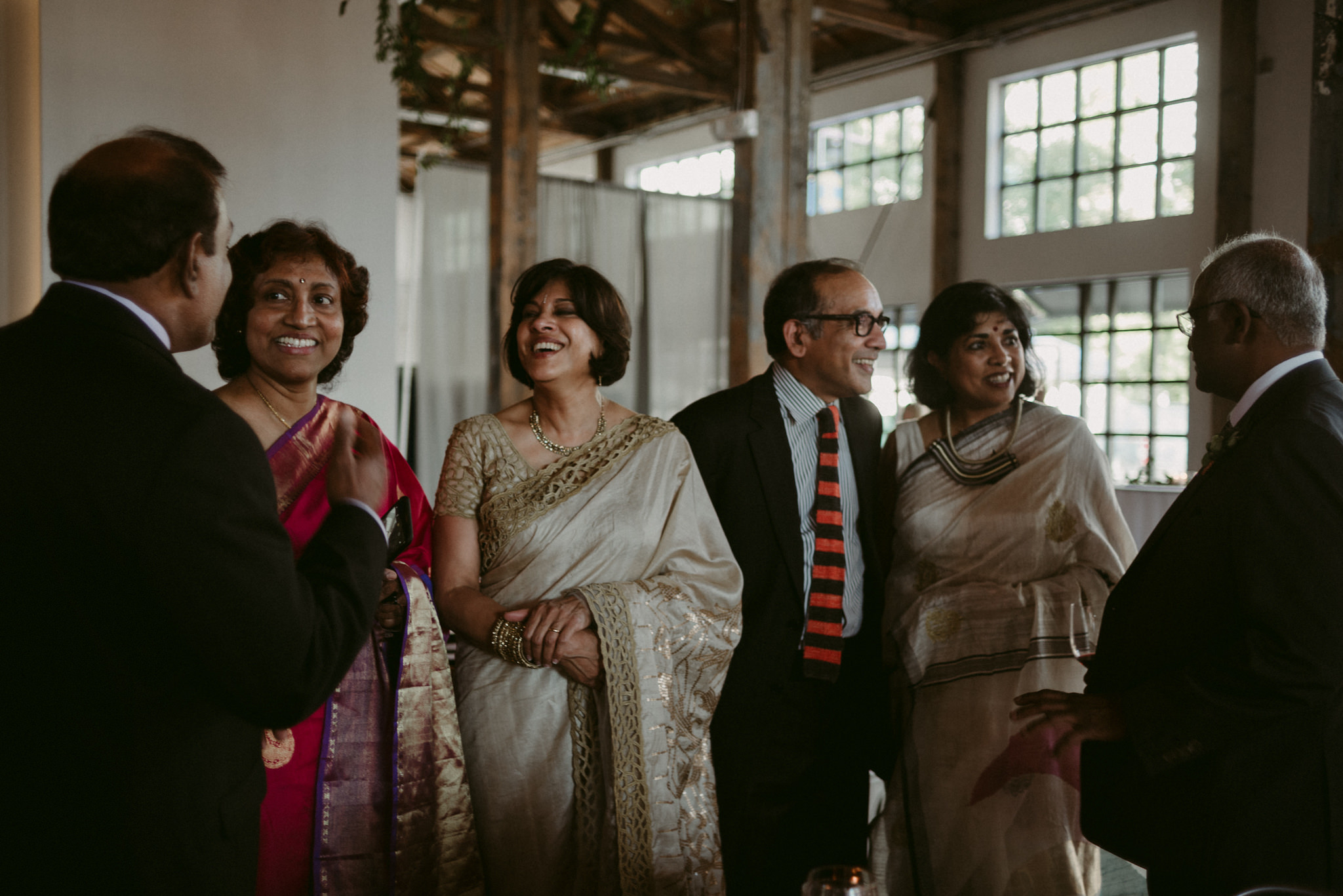 indian guests in saris laughing and talking during wedding reception