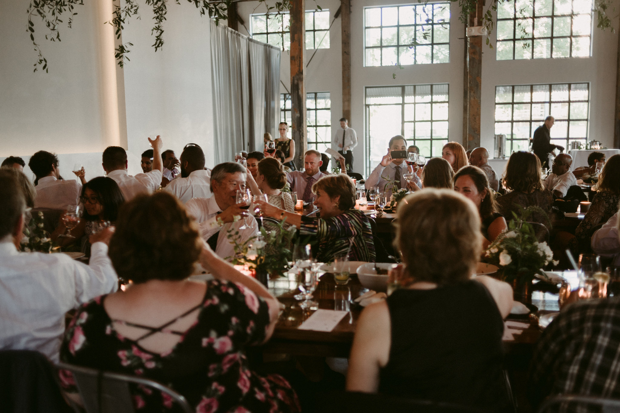 guests clinking glasses during wedding reception