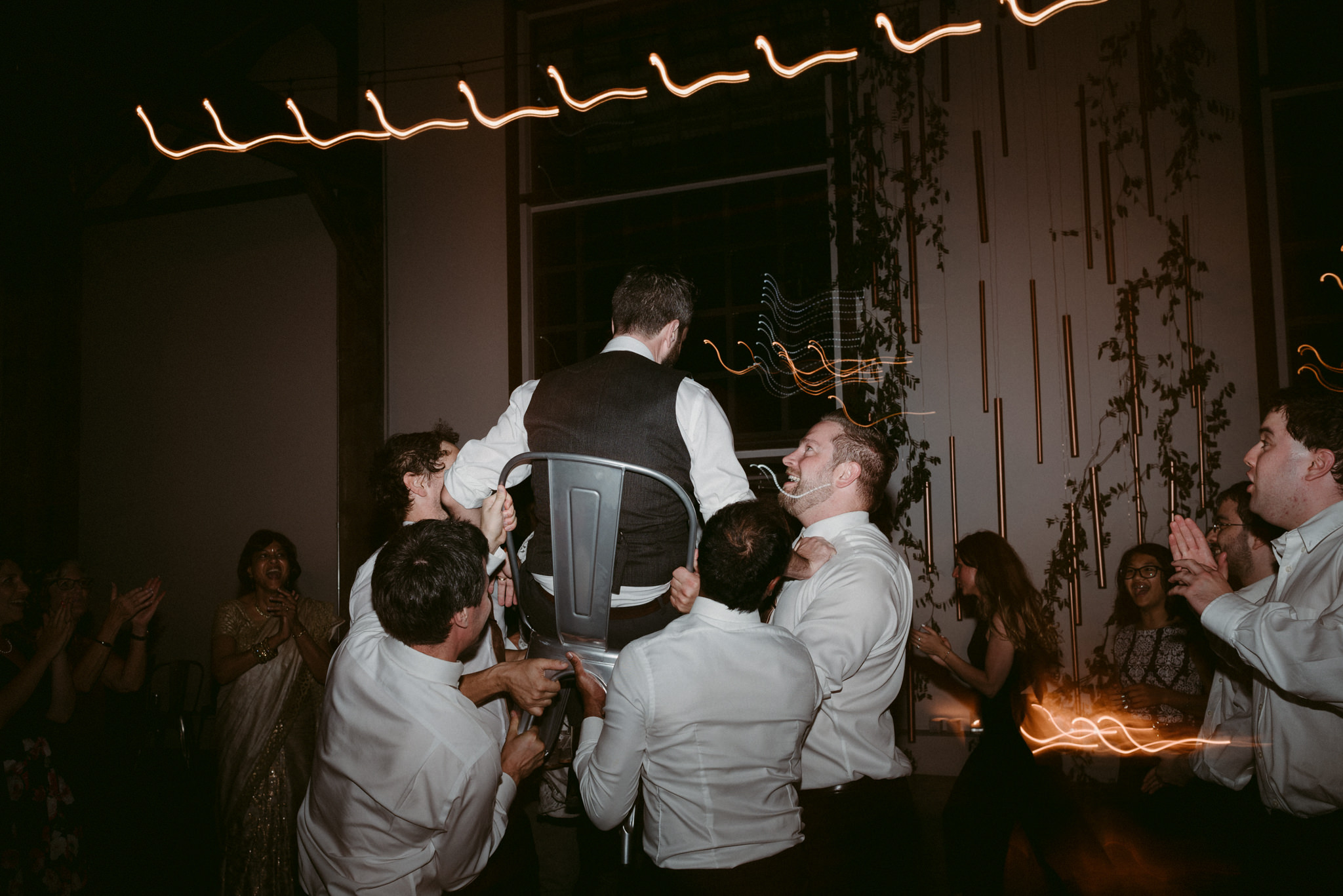 groom on chair during wedding reception