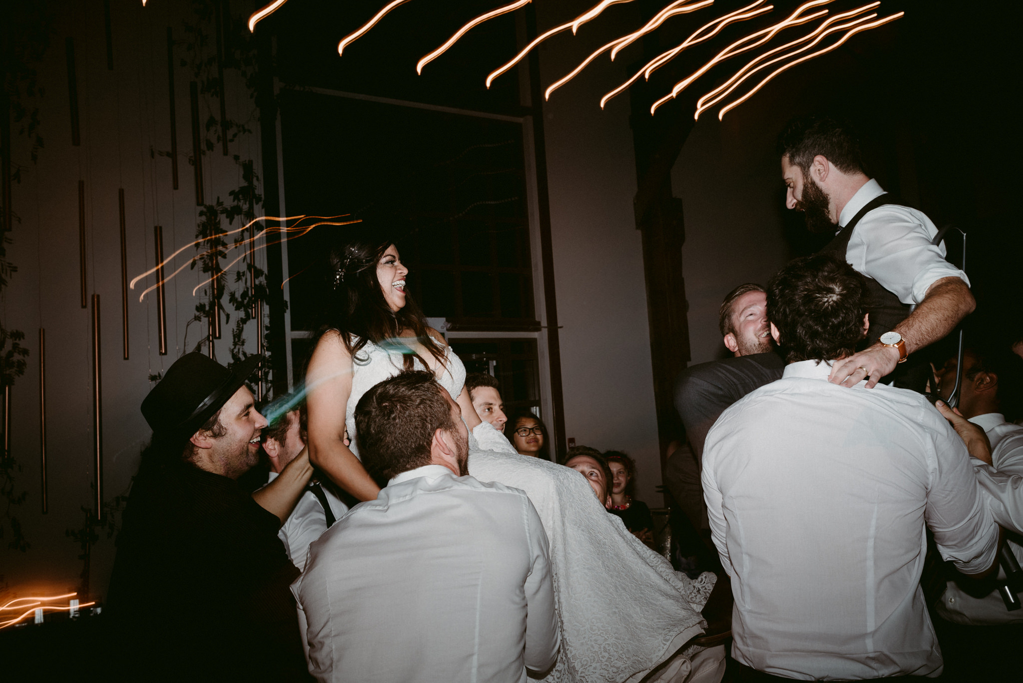 bride and groom hoisted up on chair