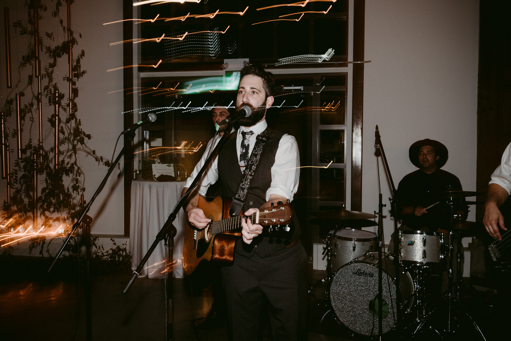 groom playing guitar and singing during wedding reception