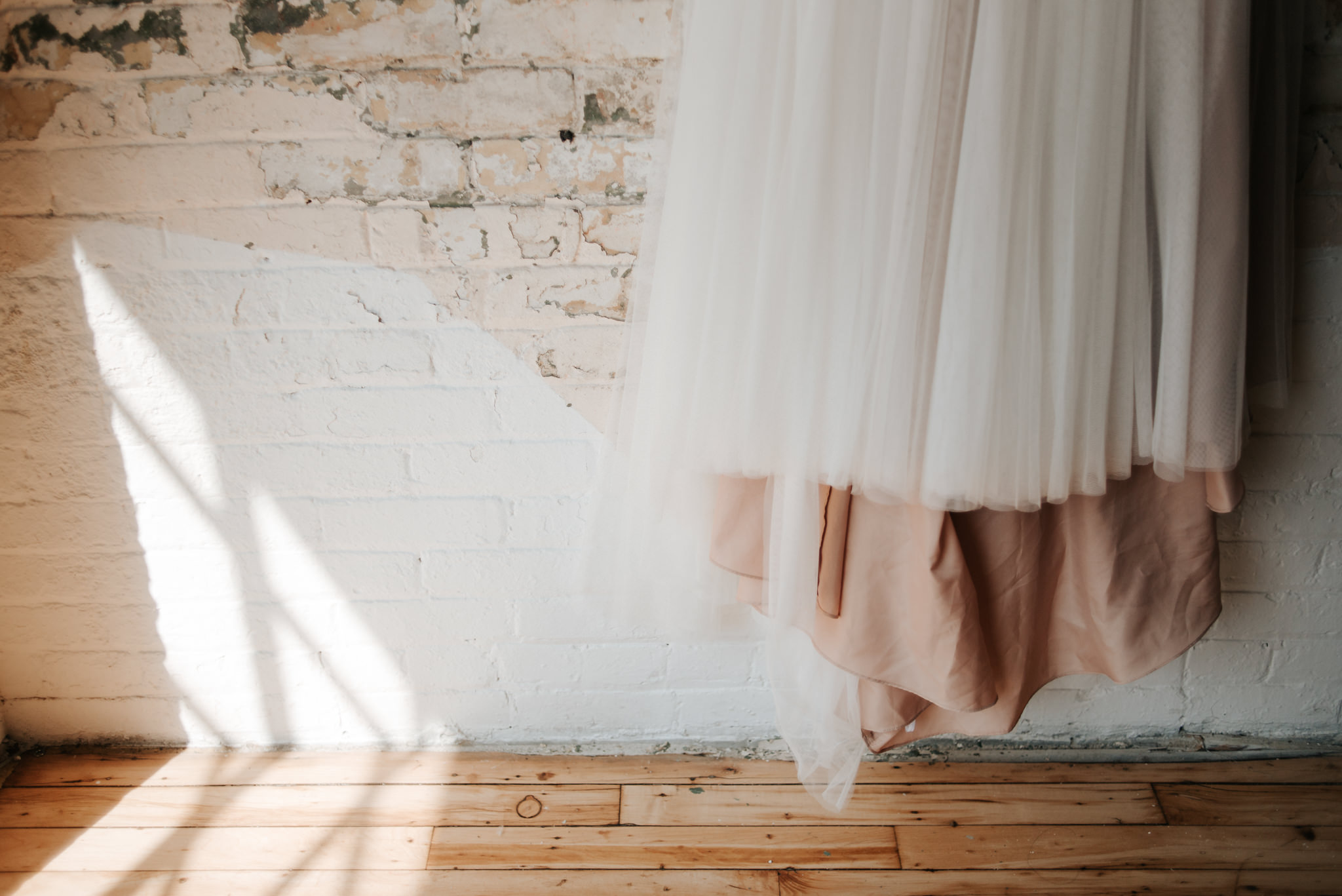 wedding dress hanging on brick wall and old wood floors of loft