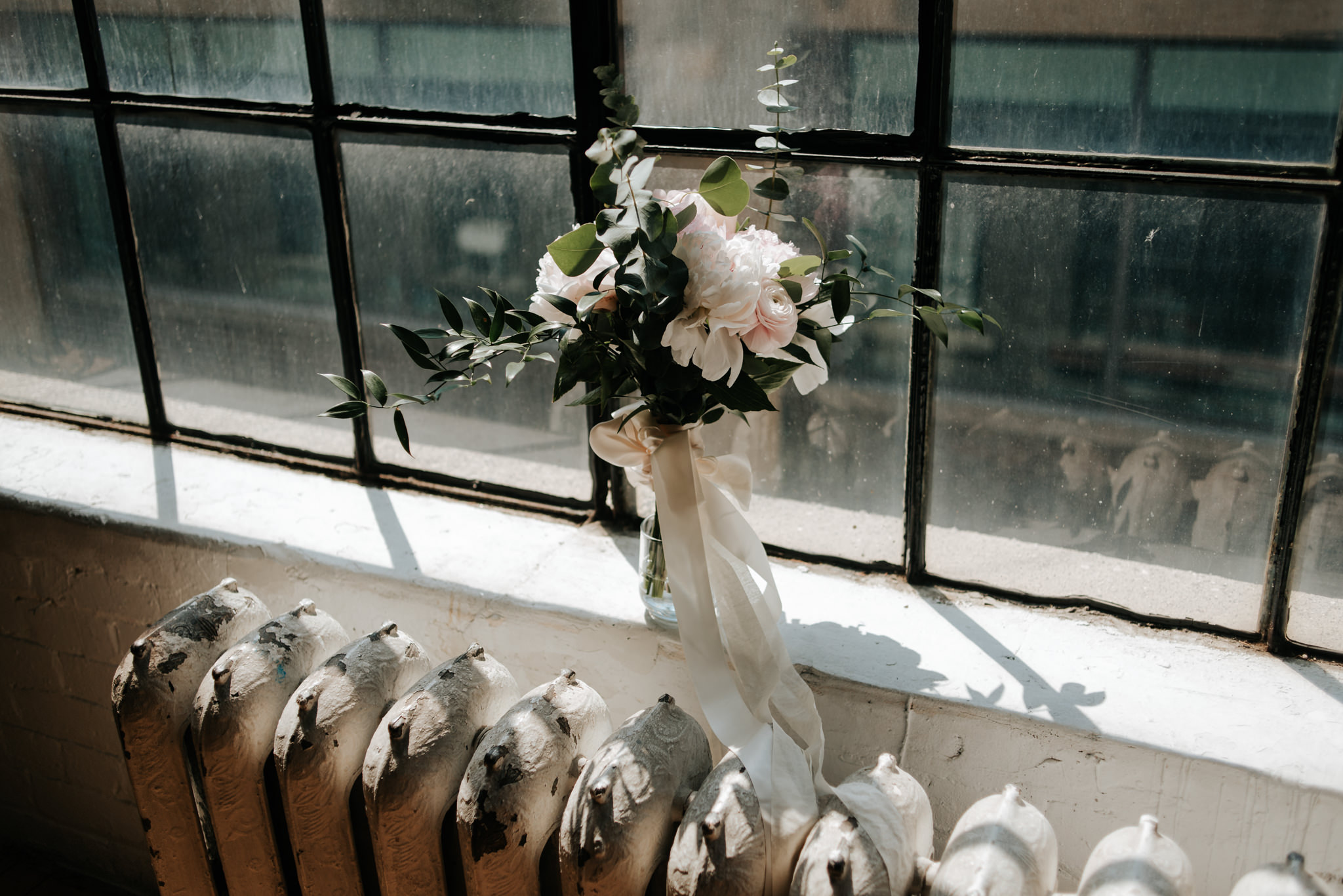 bouquet on window ledge in old loft at sunrise