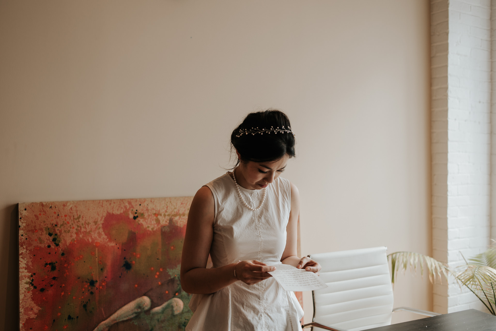 bride reading letter from groom in old loft