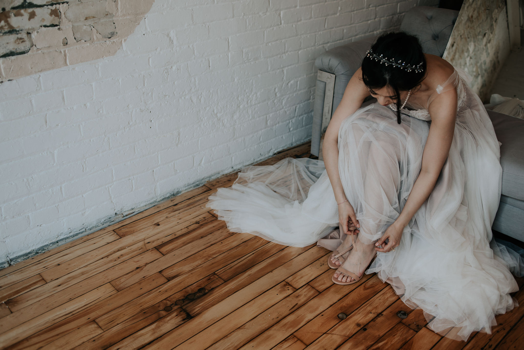 bride doing up shoes in loft
