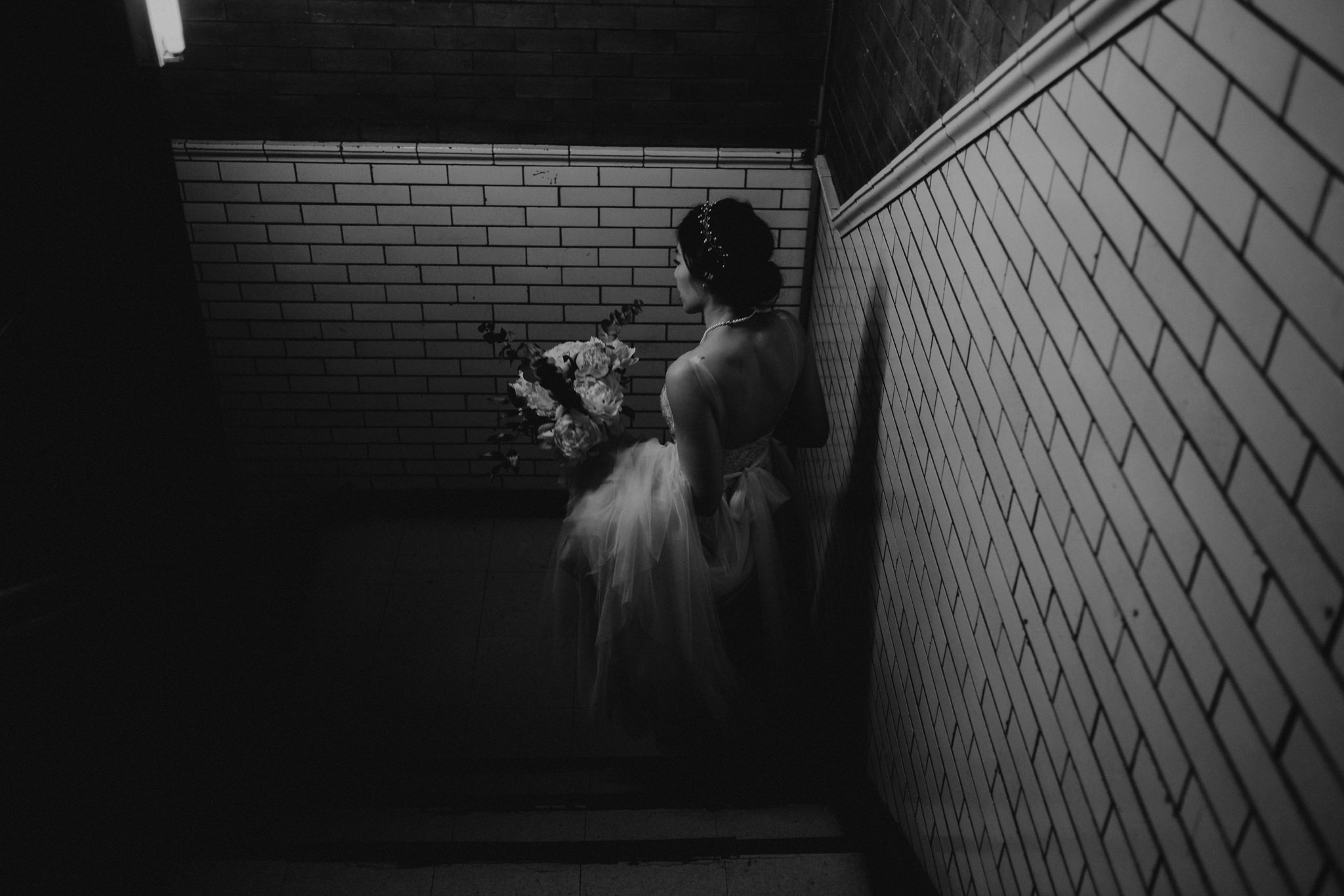 black and white of bride running on wet pavement