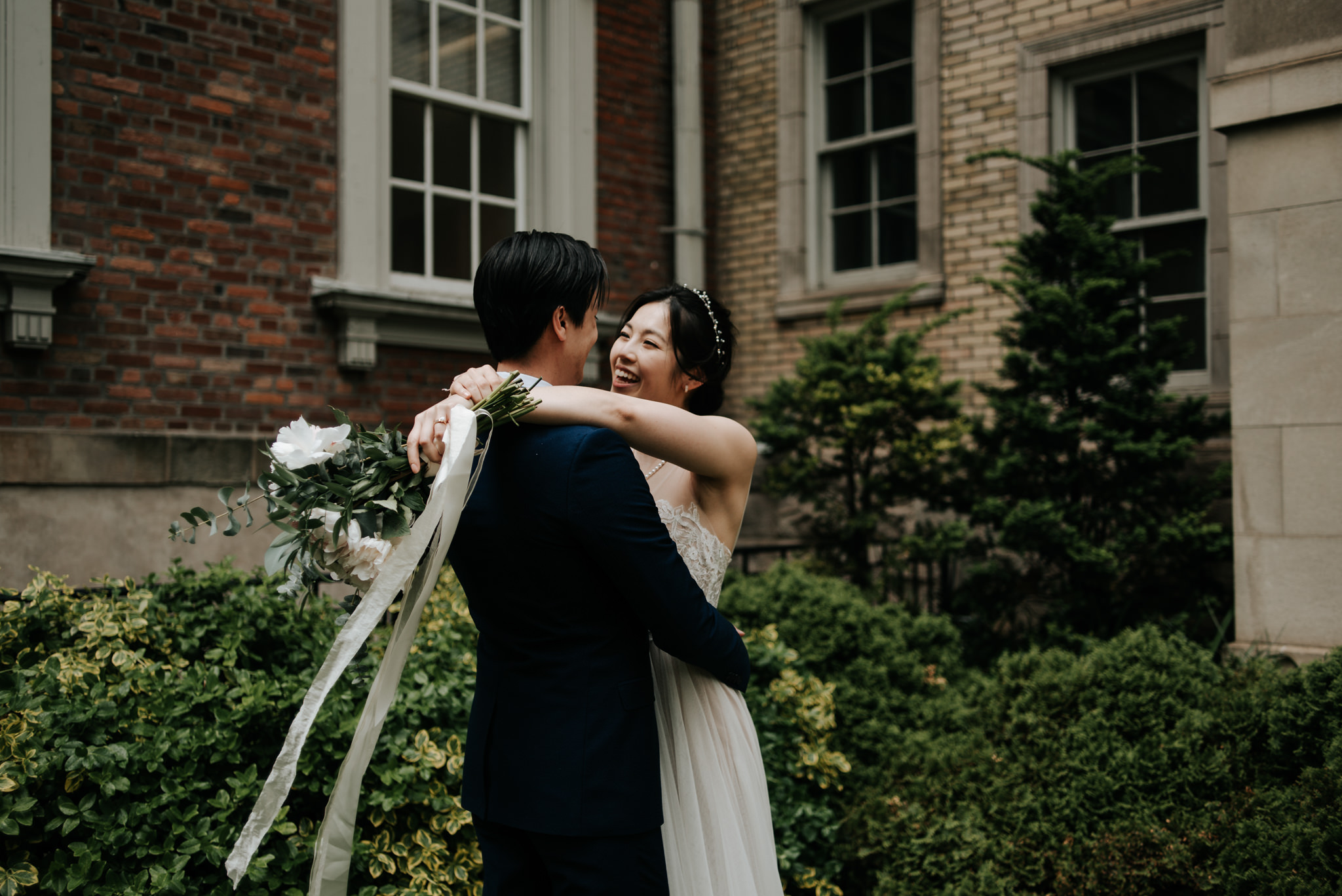 bride and groom kissing in front of old red brick building