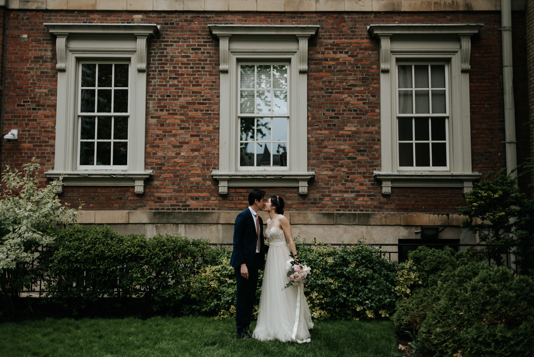bride and groom hugging and smiling in front of old building