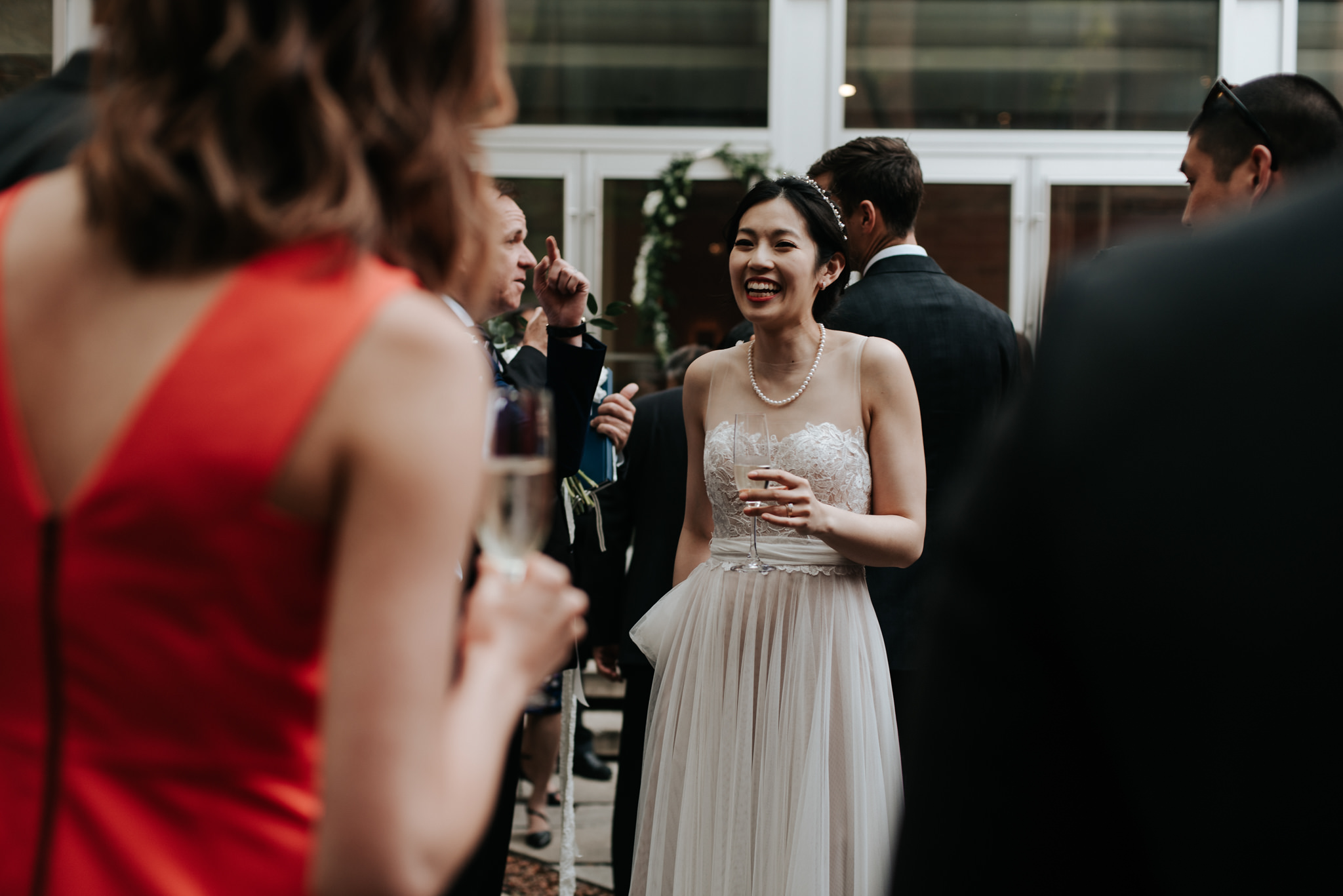 bride with champagne glass greeting guests at wedding