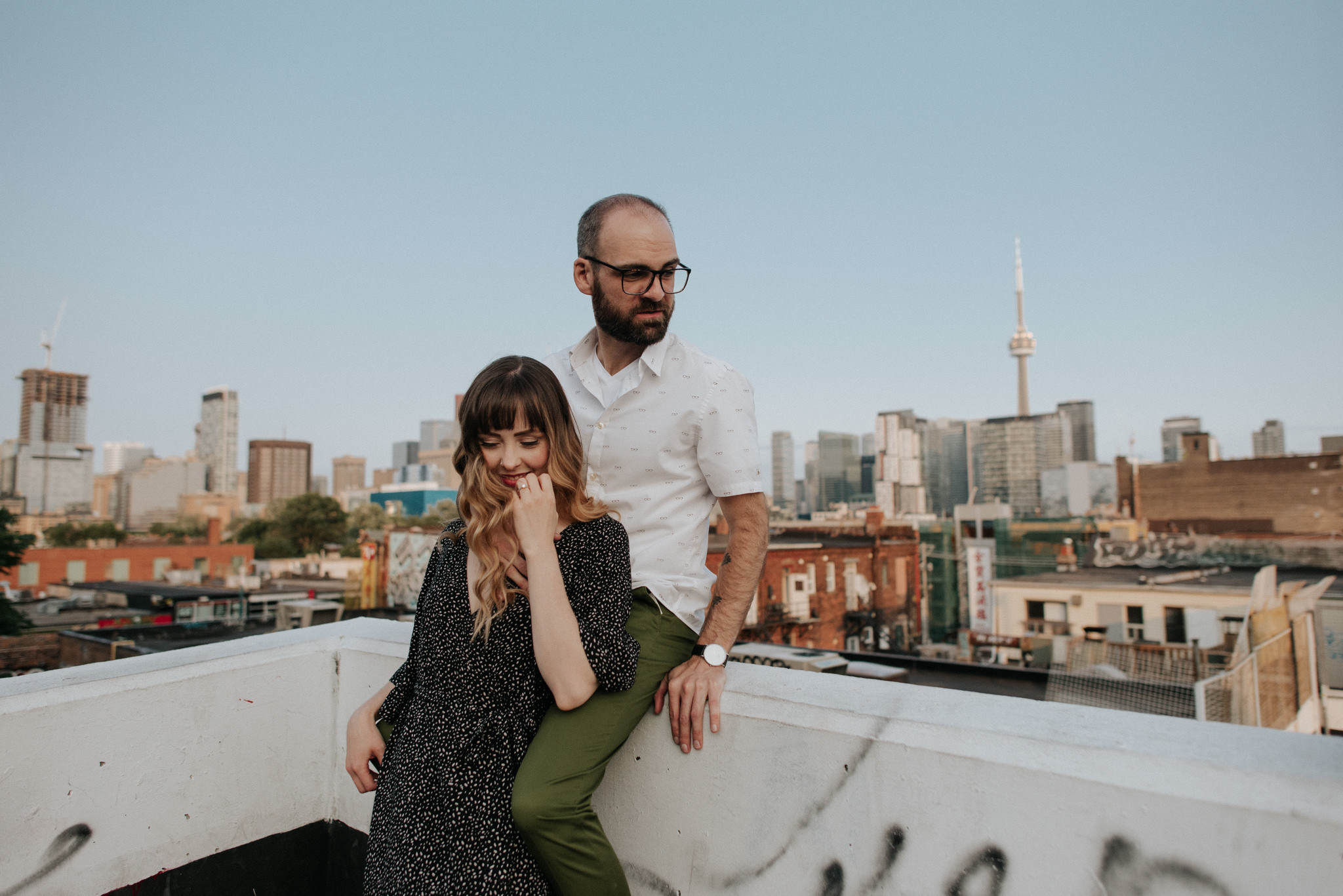 Couple on rooftop with Toronto skyline in background at sunset