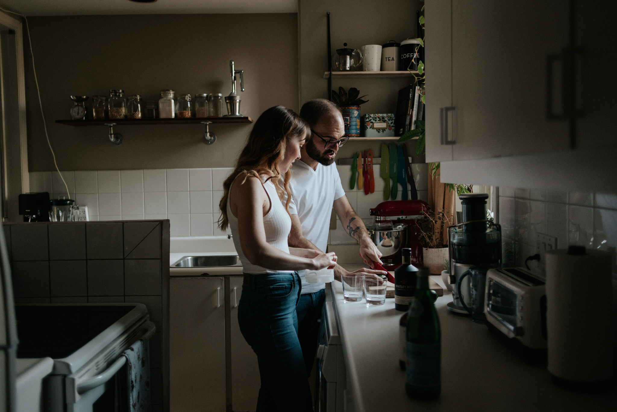 couple in their apartment making drinks