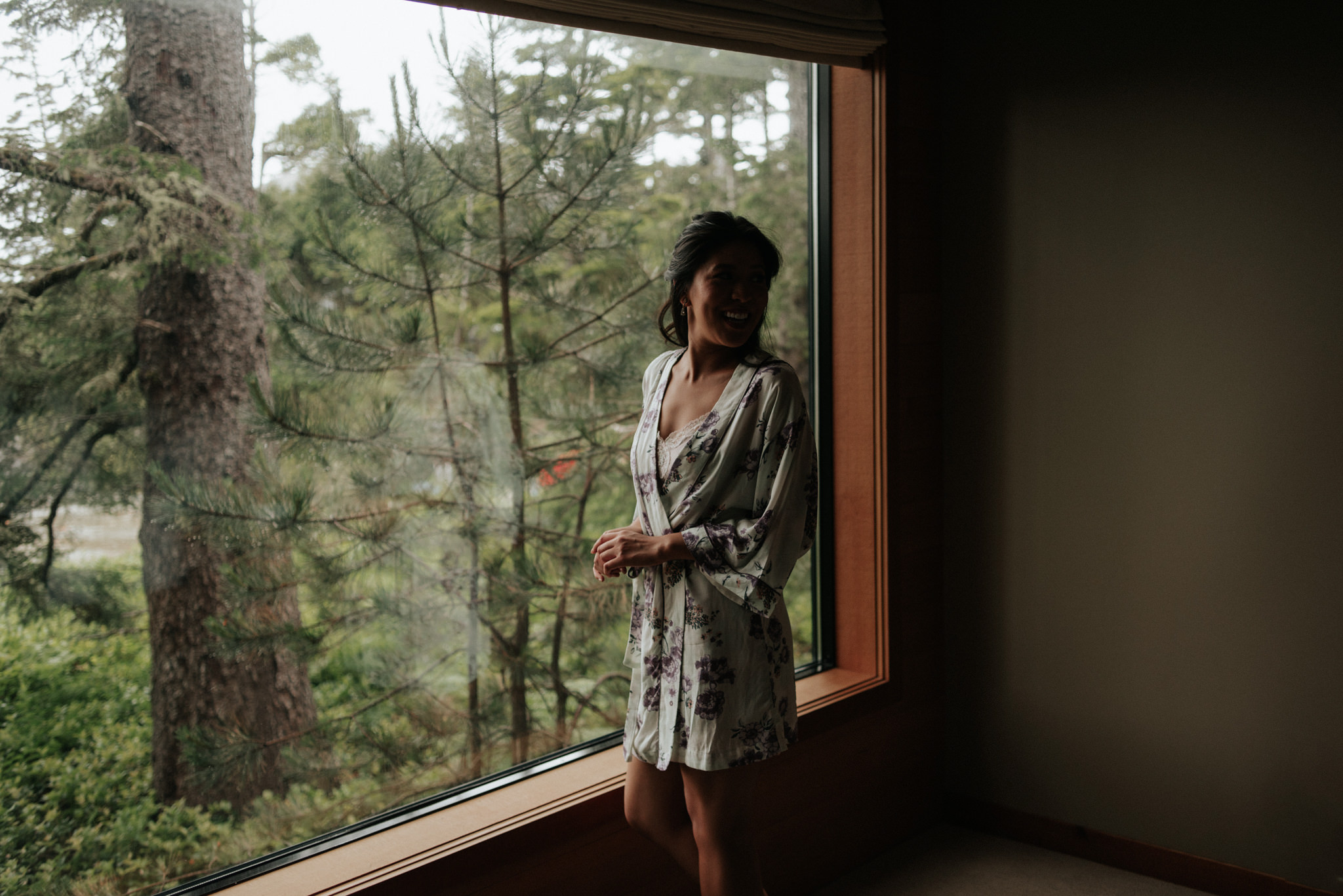 bride getting ready by window at Wickaninnish Inn for her Tofino Elopement