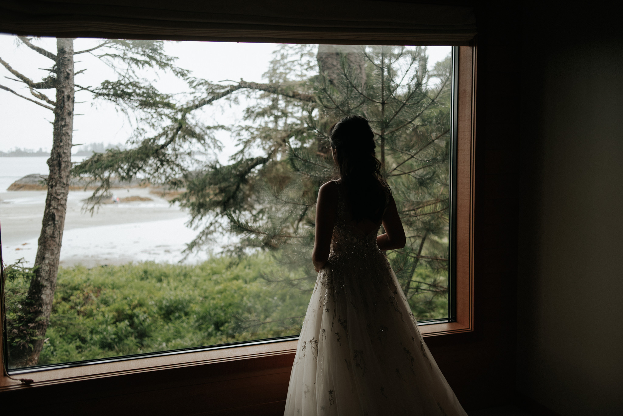 bride in wedding dress by window at Wickaninnish Inn for her Tofino Elopement