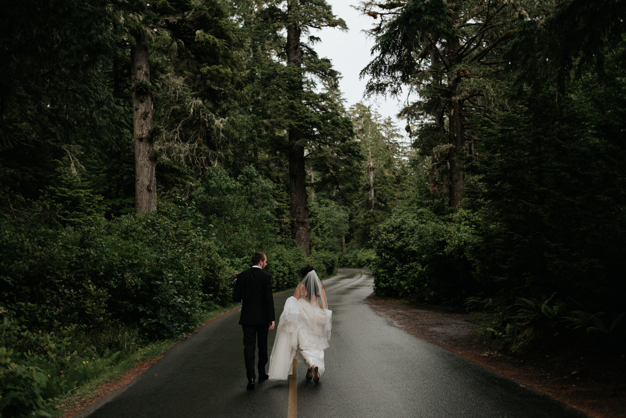 bride and groom walking down road surrounded by forest in Tofino