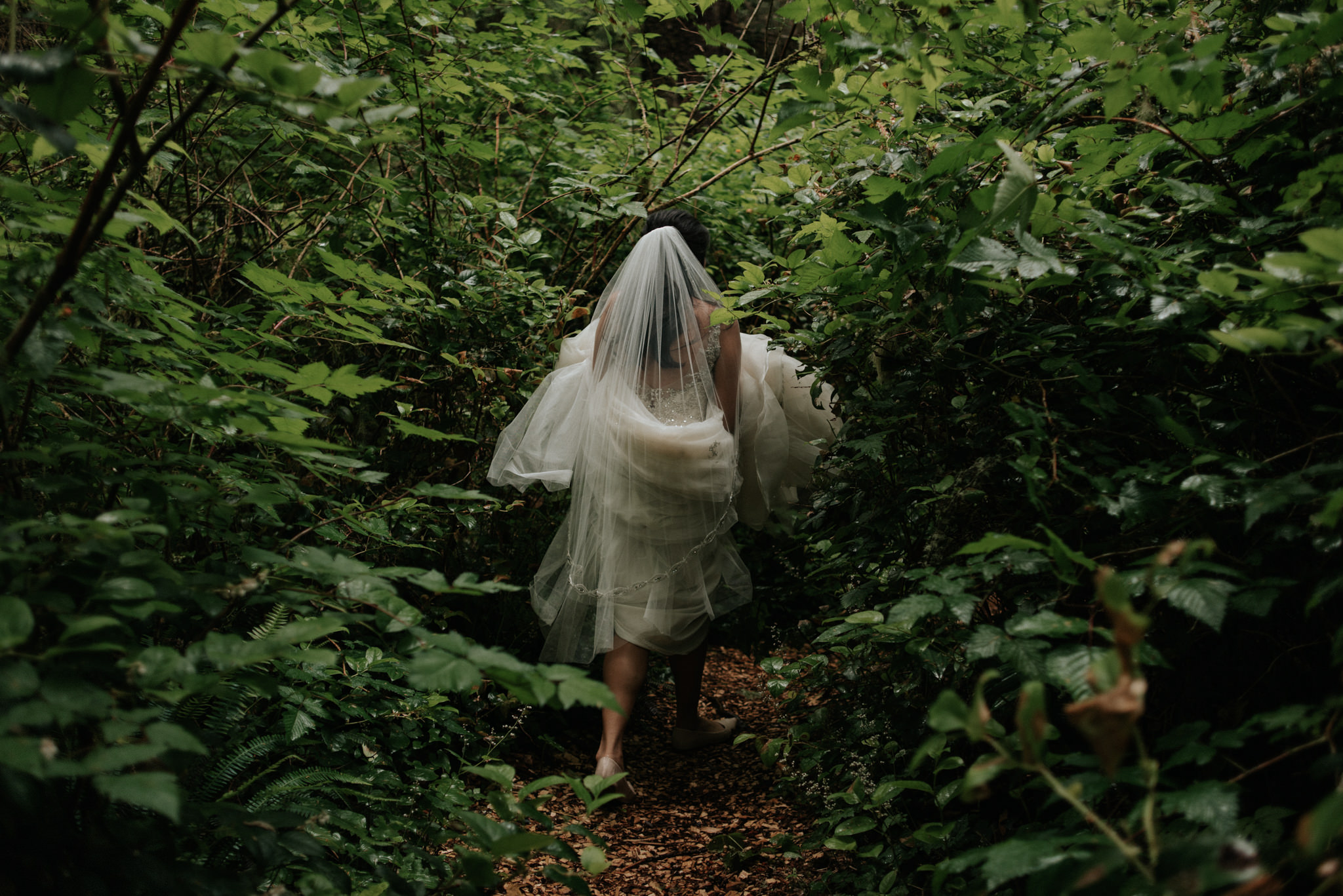 bride in wedding dress walking on forest path