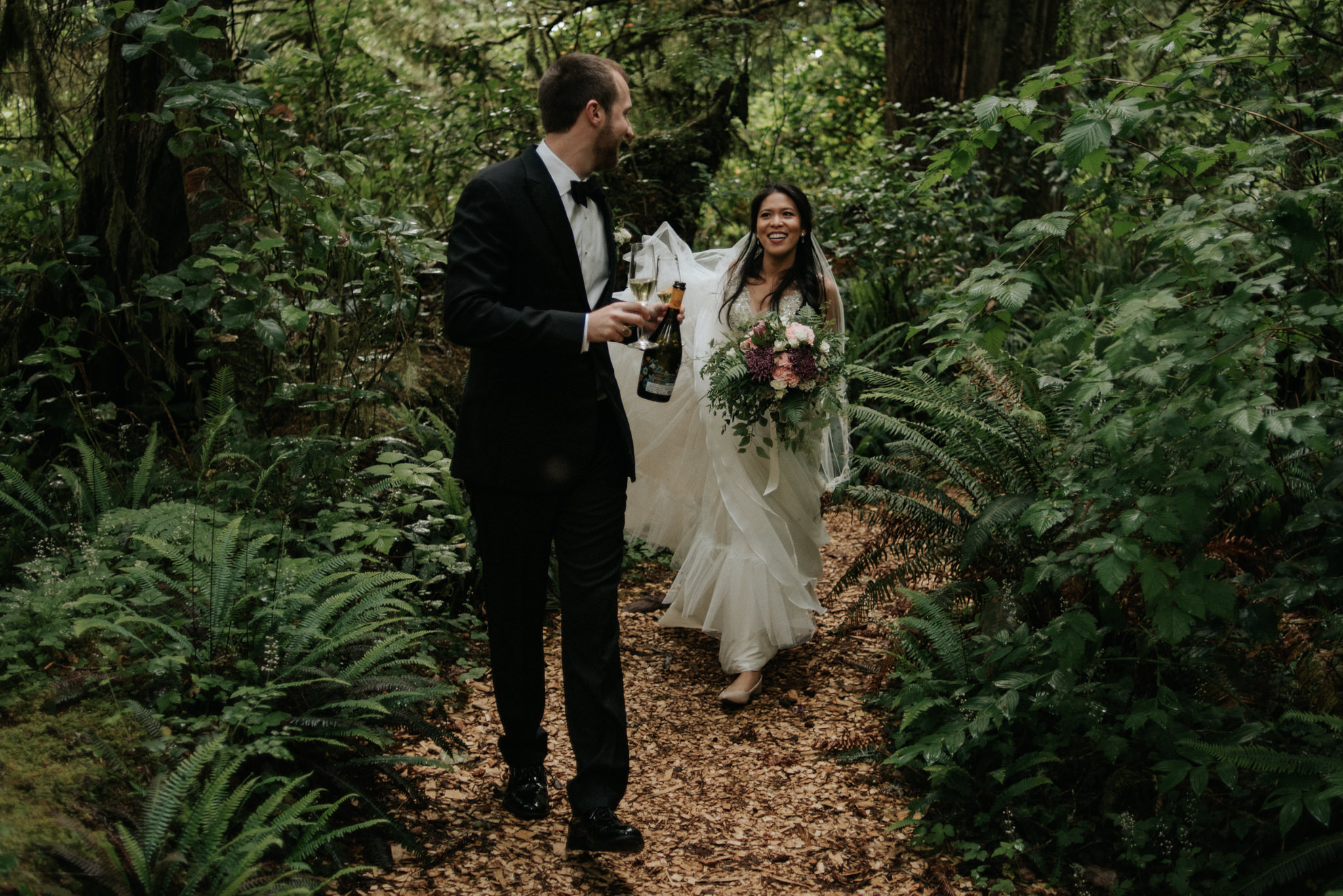 bride and groom drinking champagne after wedding ceremony in forest in Tofino