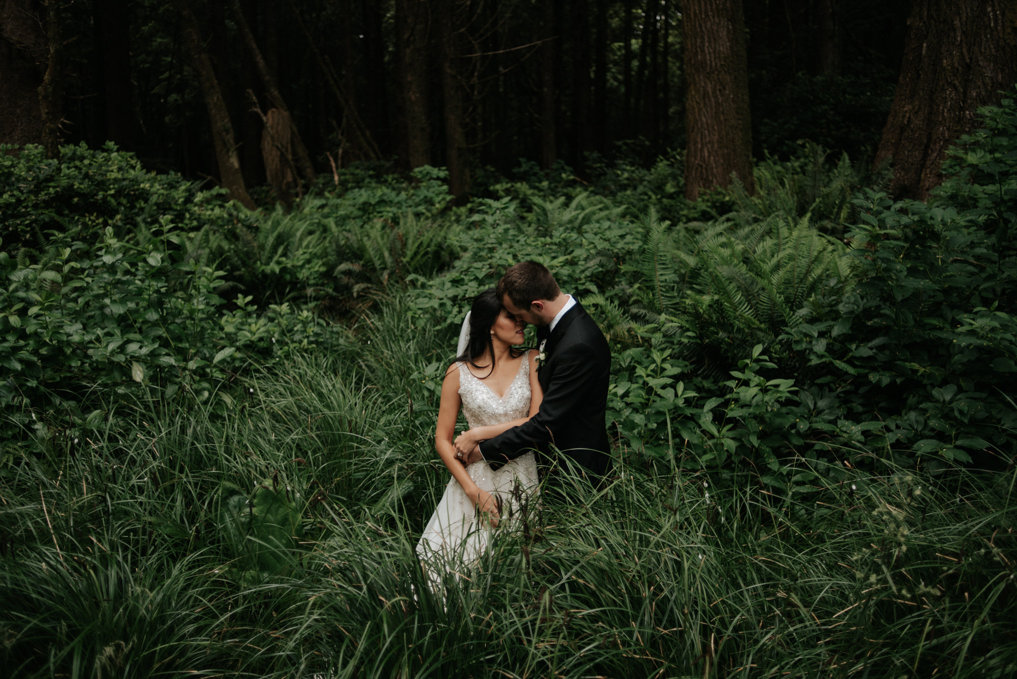 Couple standing in sea grass in forest in Tofino