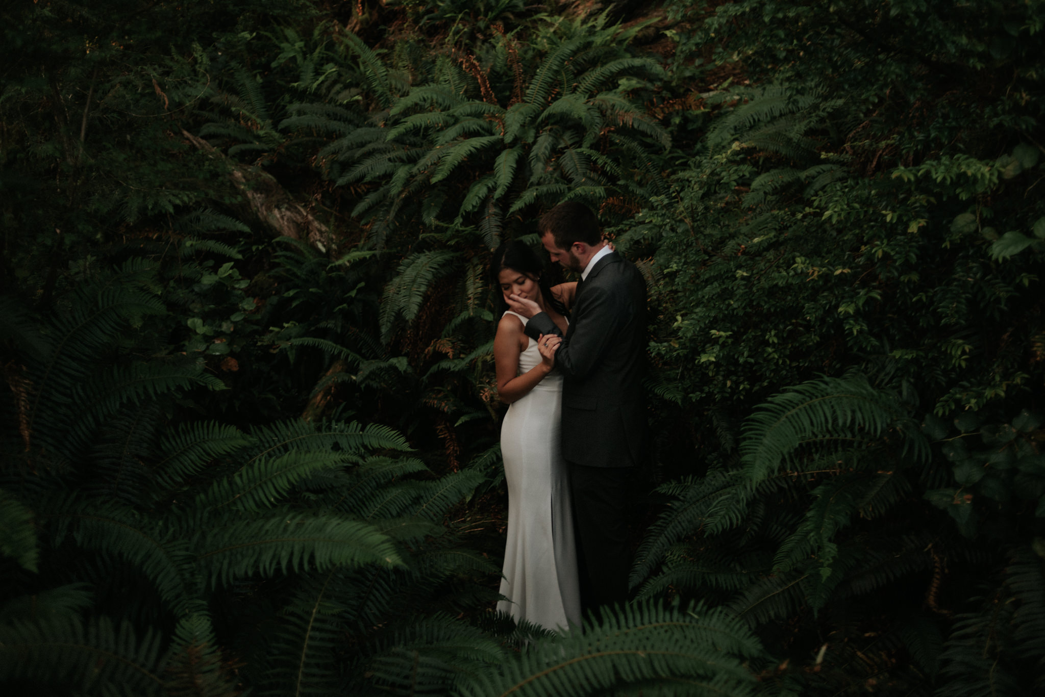couple standing in ferns on wedding day