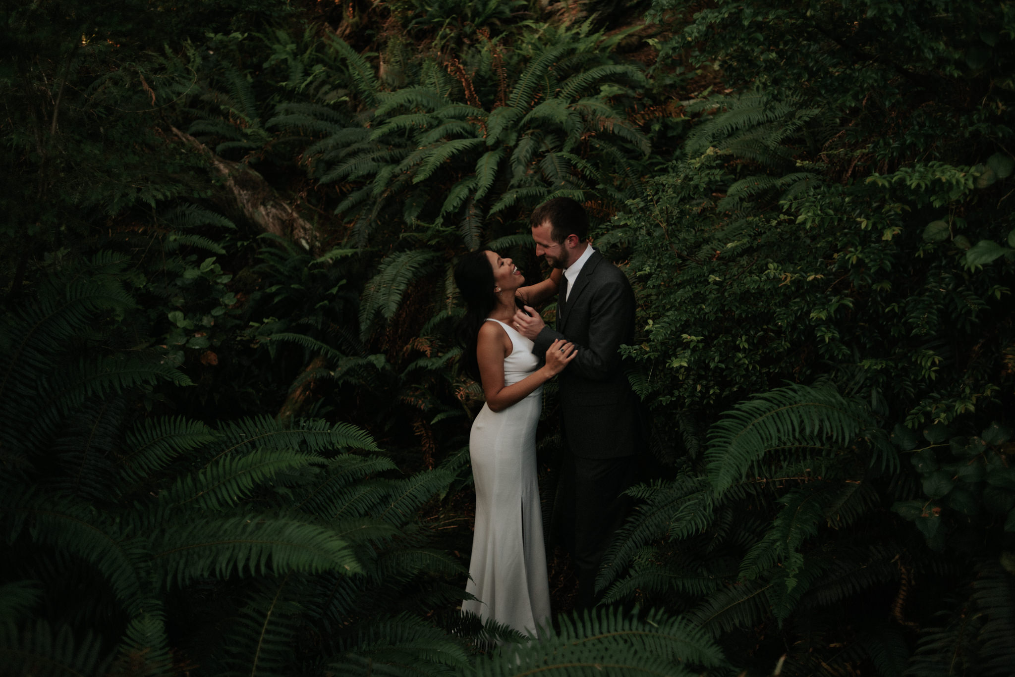 bride and groom holding hands in forest in Tofino