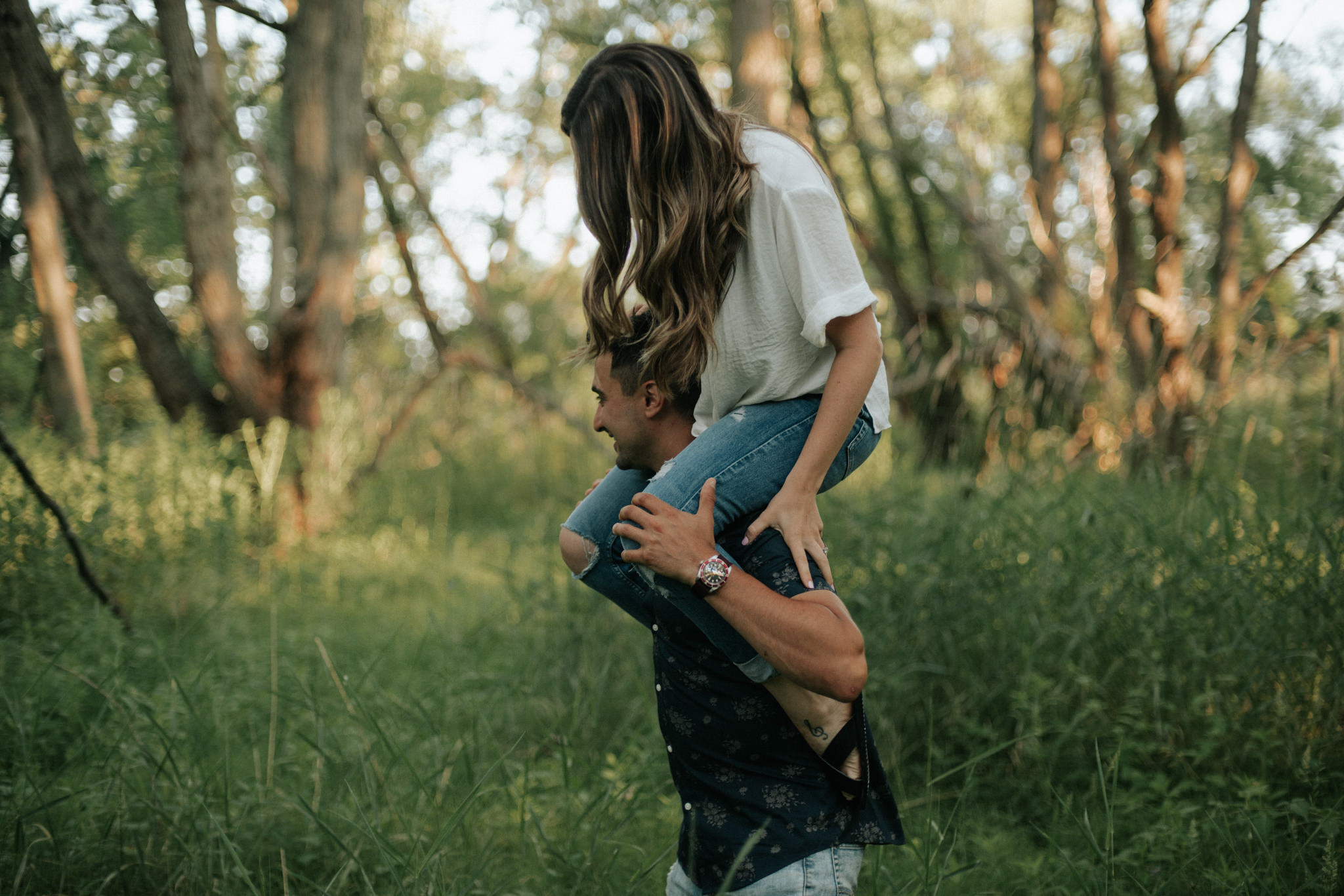 girl sitting on guy's shoulders in a forest