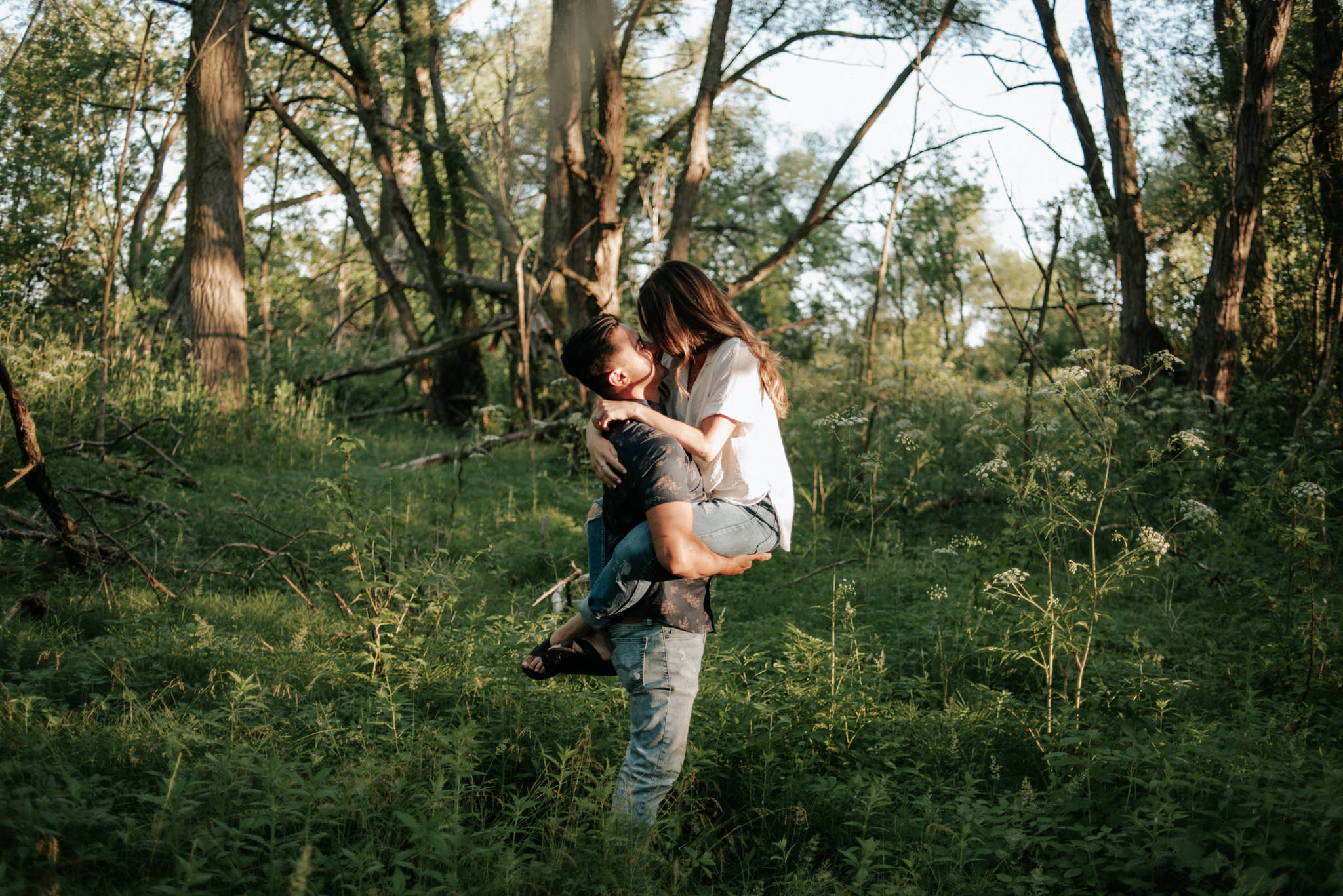 guy holding up girl while standing in forest
