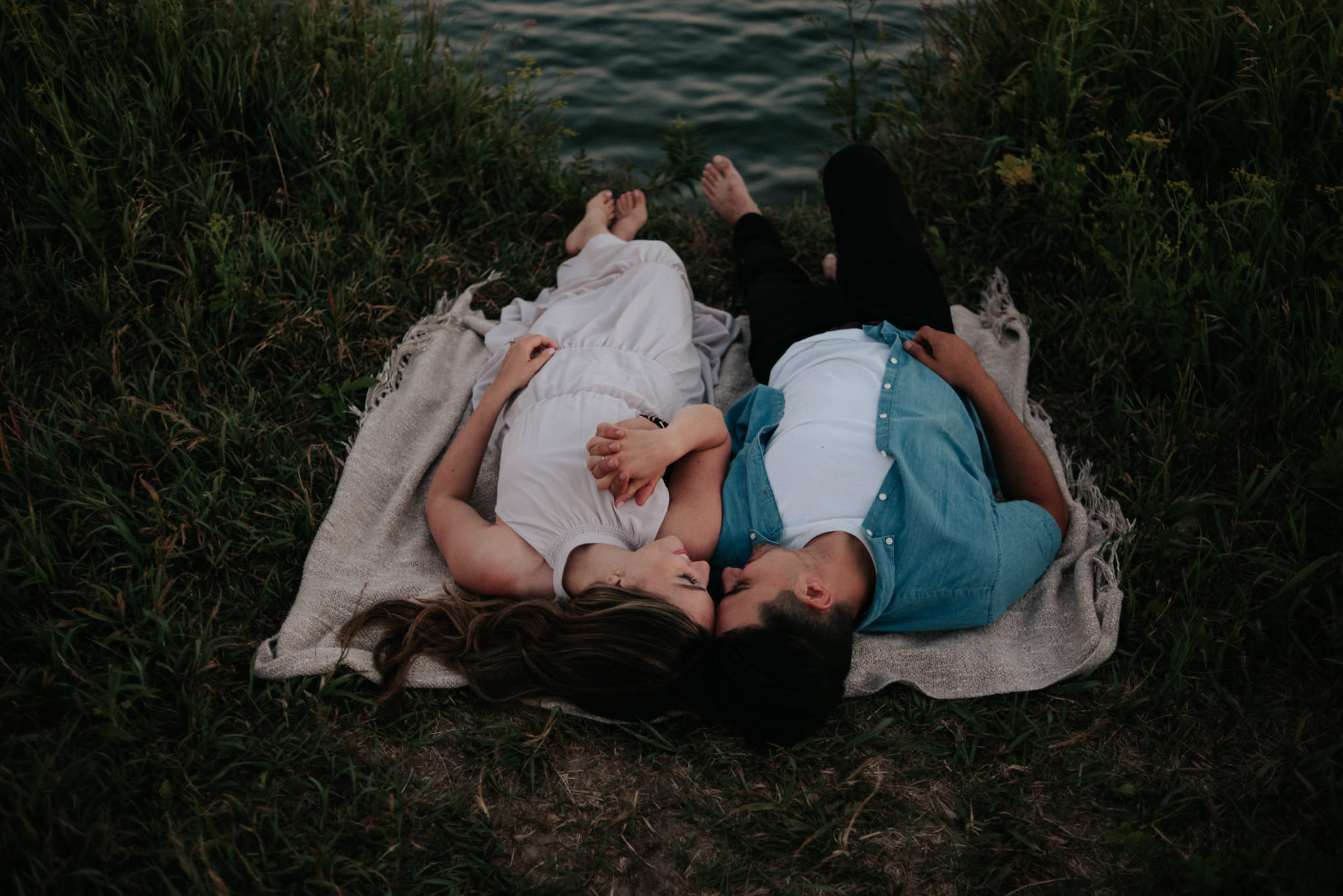 couple lying down on ground on blanket by the lake at sunset